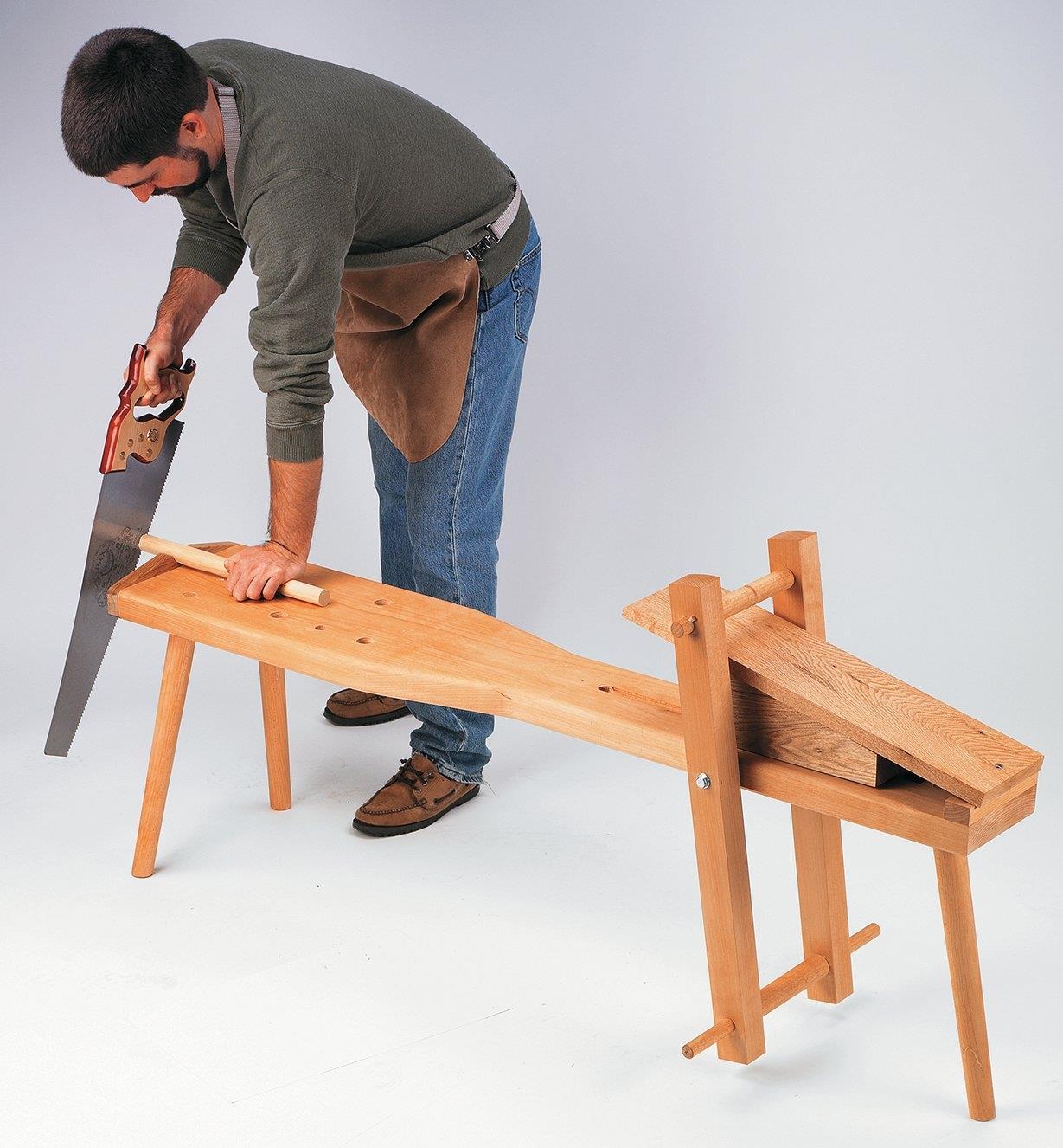 Homme utilisant un banc d'âne pour couper un goujon