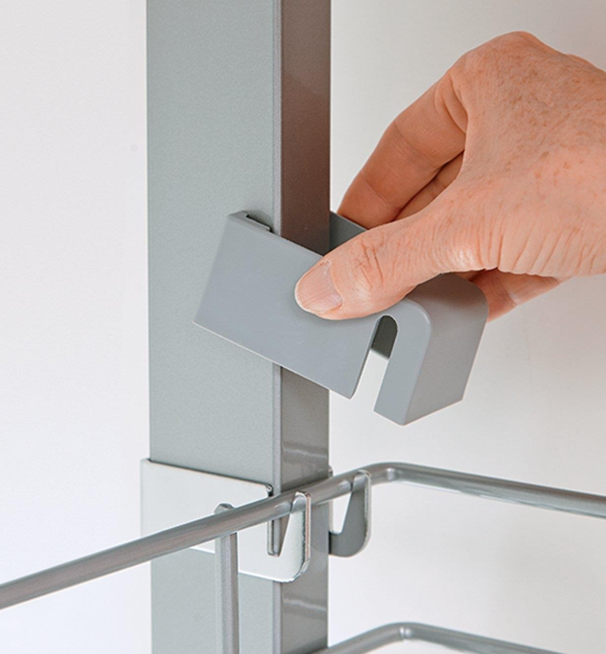 Sliding on a clip to hold a shelf in place on the pantry unit