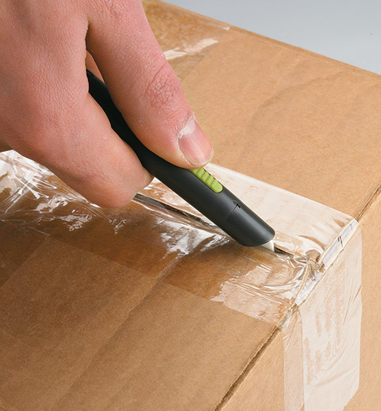 Desk Utility Cutter being used to slice through packing tape on a cardboard box
