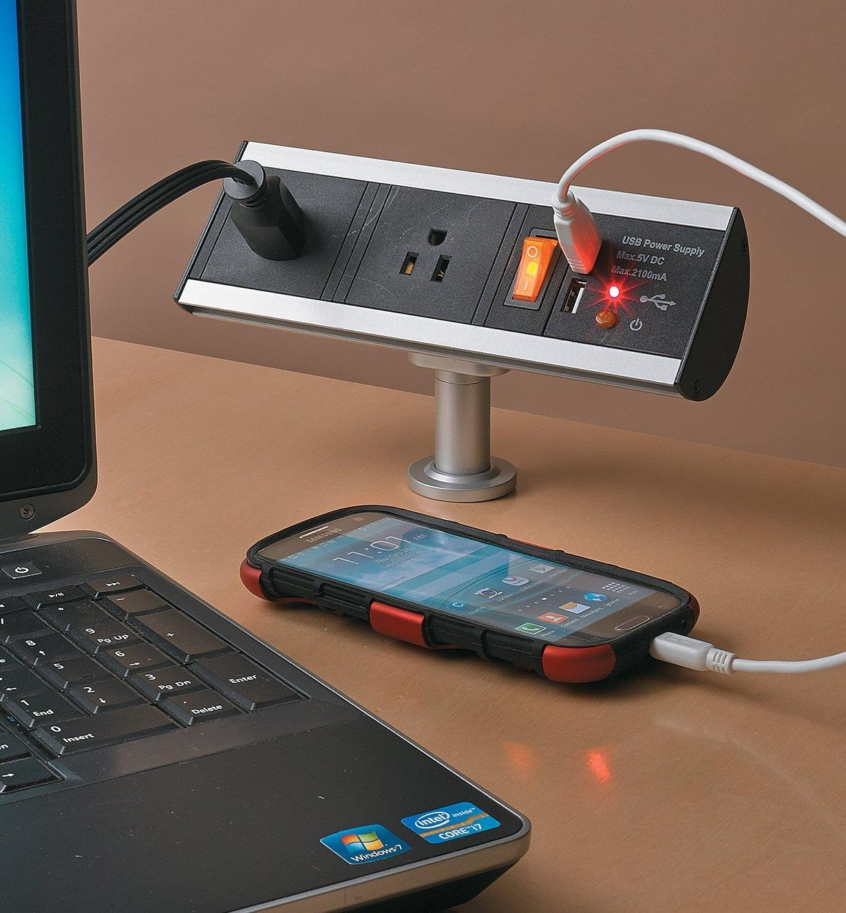 Cell phone and laptop plugged into a Stand-Off Power Bar installed in a desk