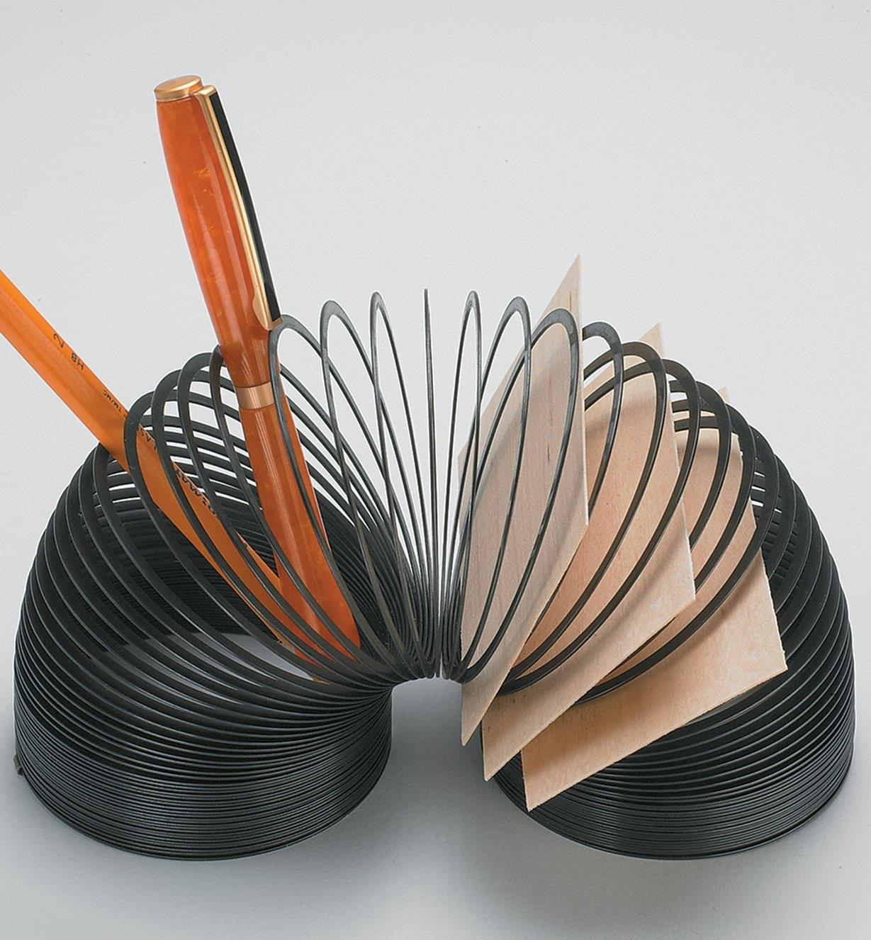 A Slinky used to hold a pen, pencil and business cards