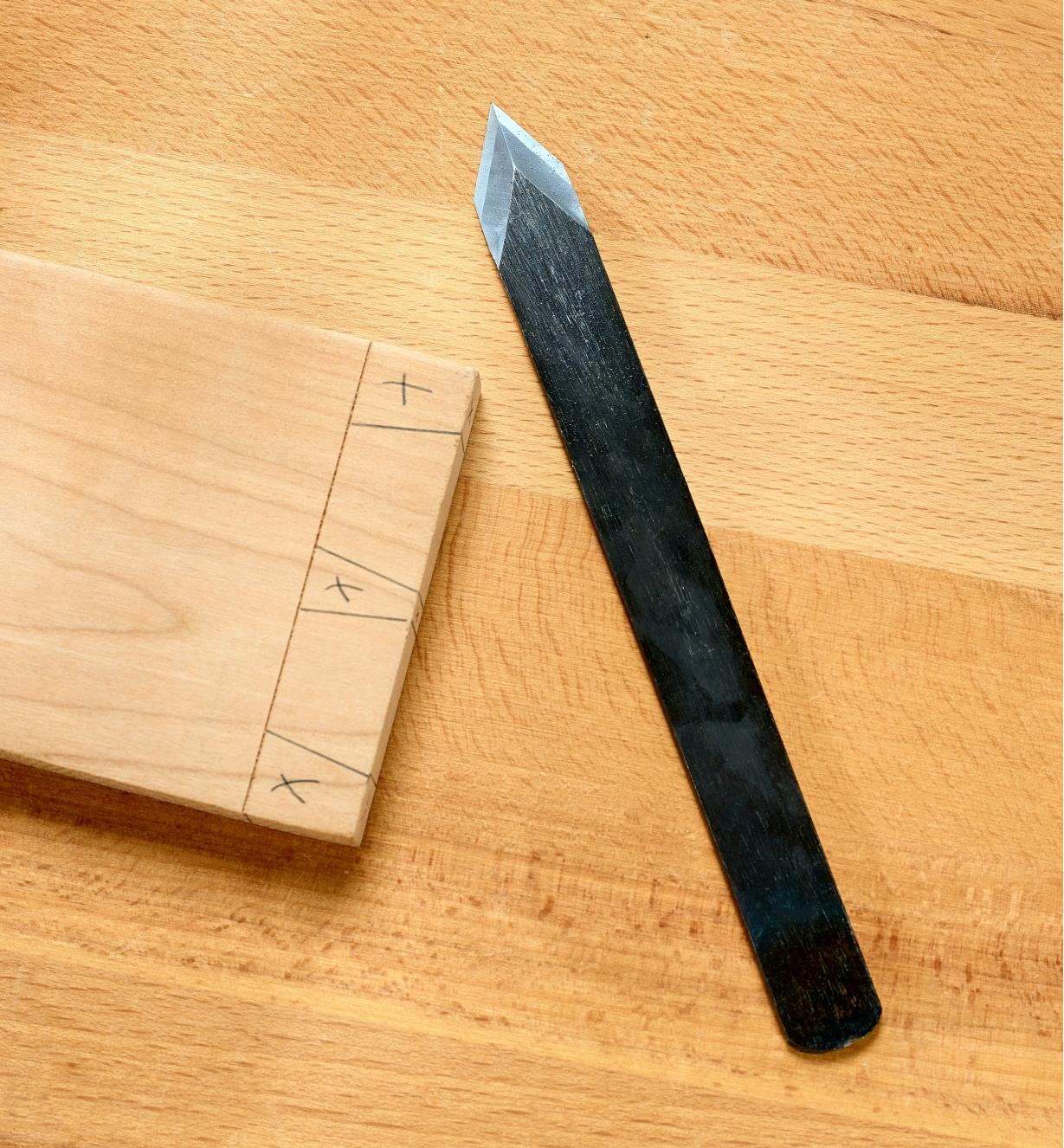 Japanese spear-point marking knife on a workbench beside a piece marked for cutting dovetails