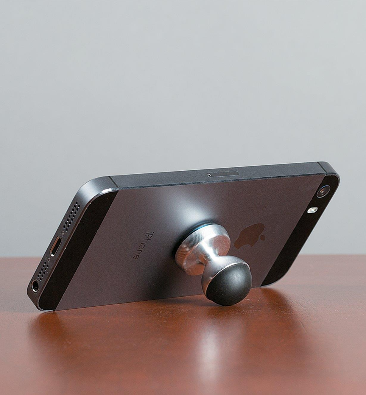 HobKnob attached to the back of a phone holding it at an angle on a table