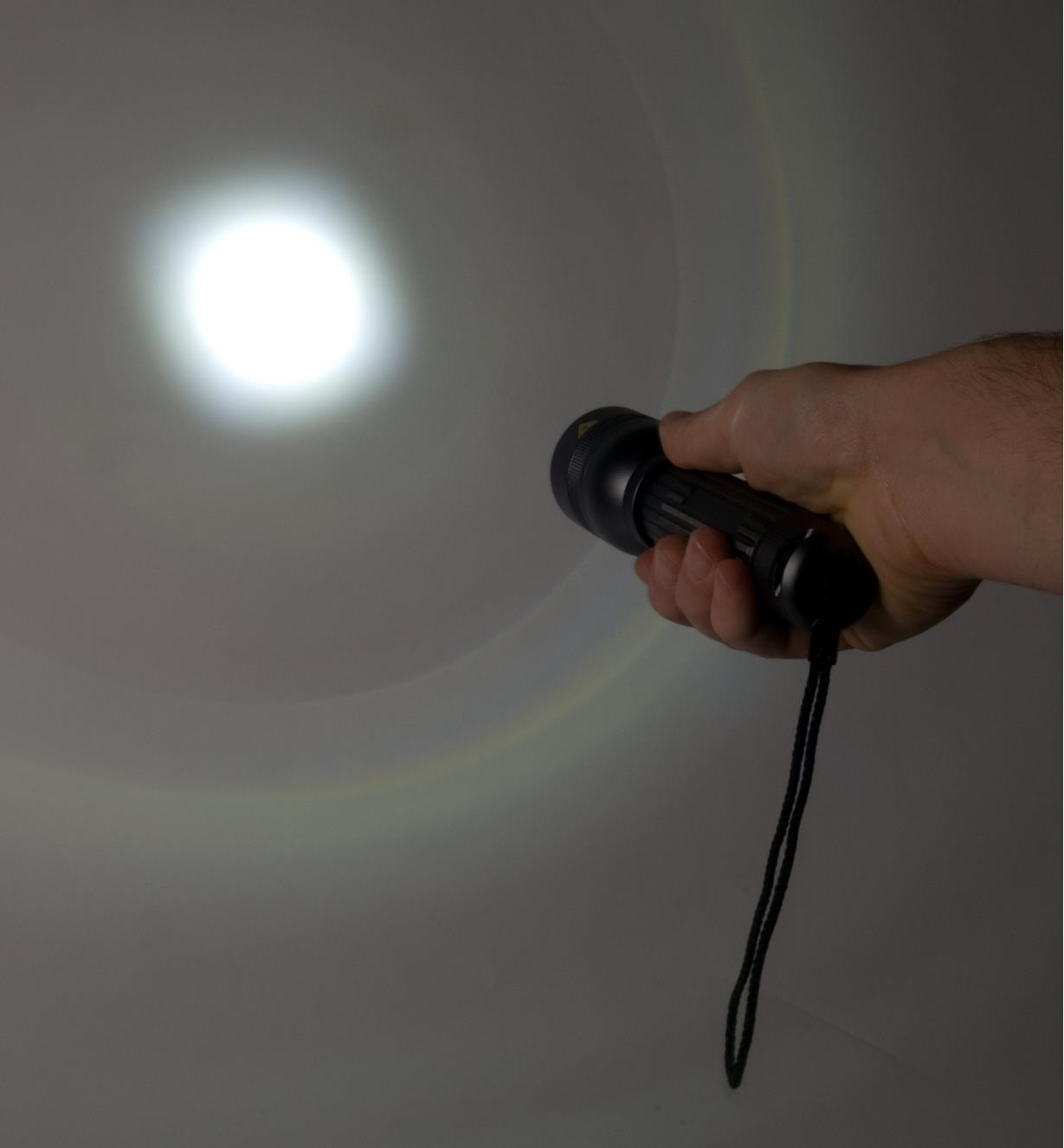 Flashlight shines a narrow spotlight on a wall