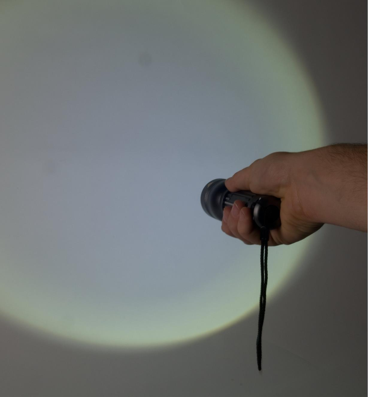 Flashlight shines a wide-area floodlight on a wall