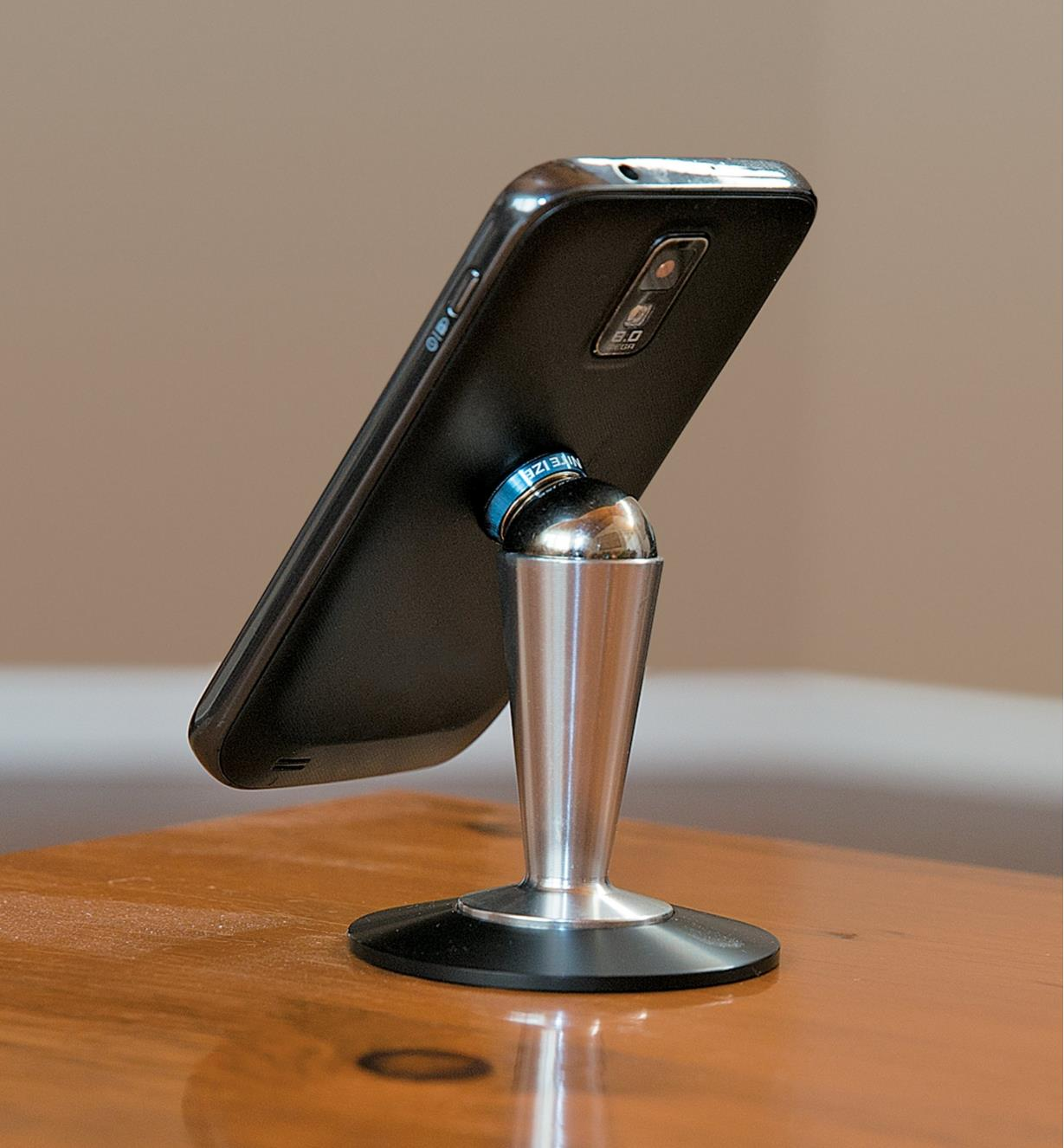 Phone attached to desktop pedestal, rotated to portrait orientation.