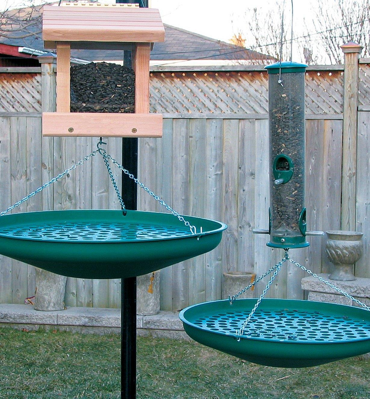 Two Seed Saucers hanging under a bird house and a tube feeder