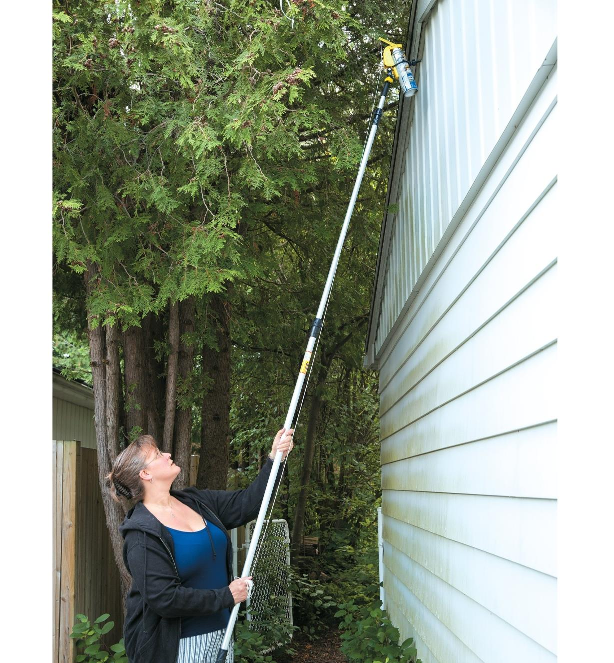 A woman holds a pole with a spray can attached to reach the upper level of a house