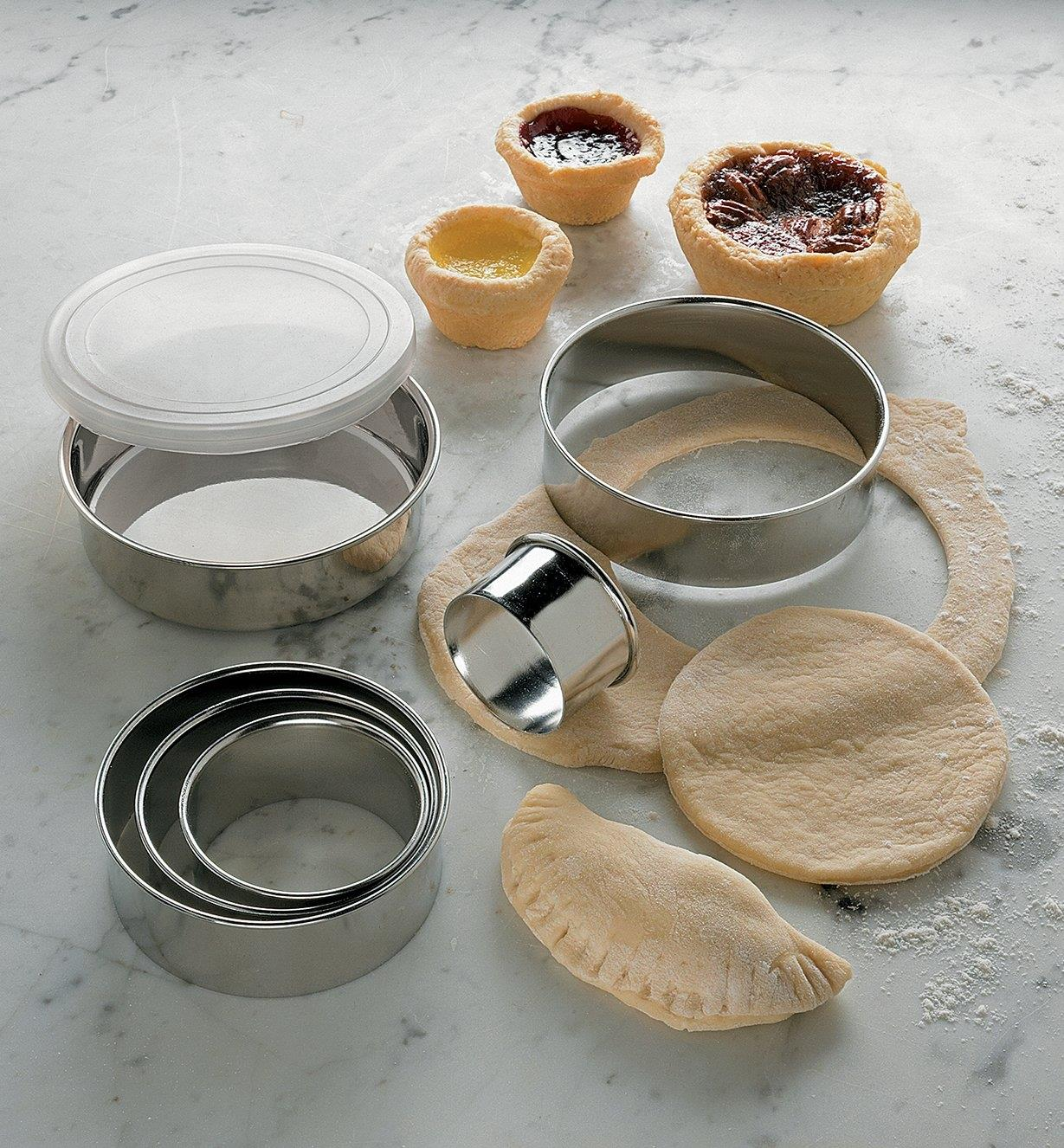 Stainless Steel Pastry Cutters on a counter being used to cut pastry circles, with baked tarts in the background