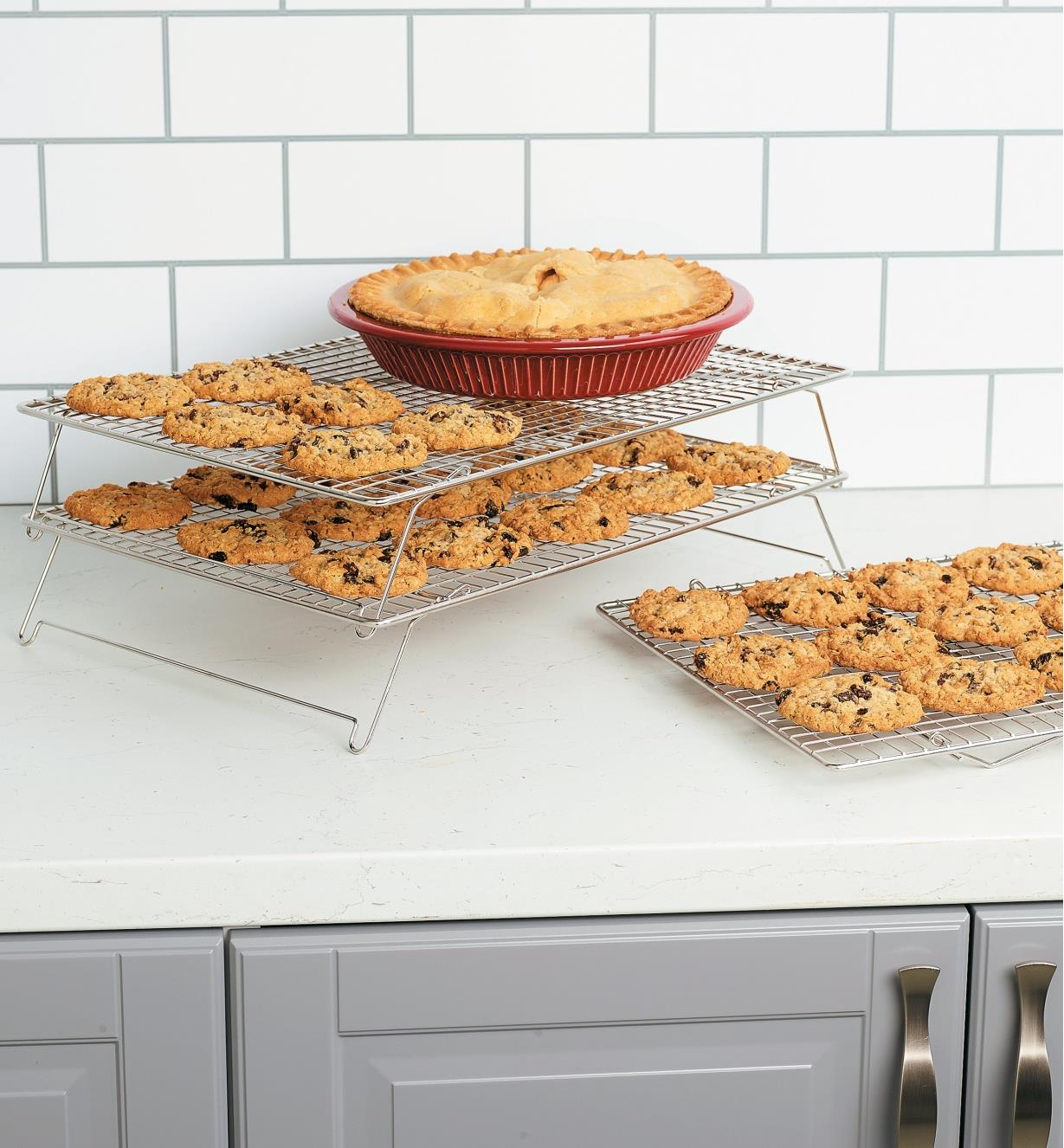 Two stacked racks holding cookies and a pie next to a third rack sitting on the counter, holding cookies