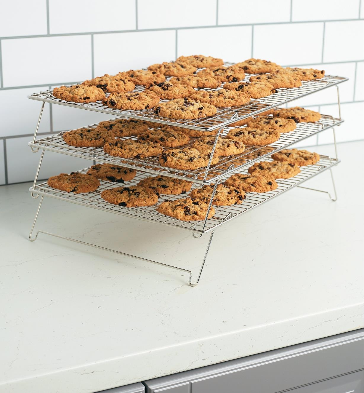 Cooling racks stacked in three tiers with each rack covered in cookies