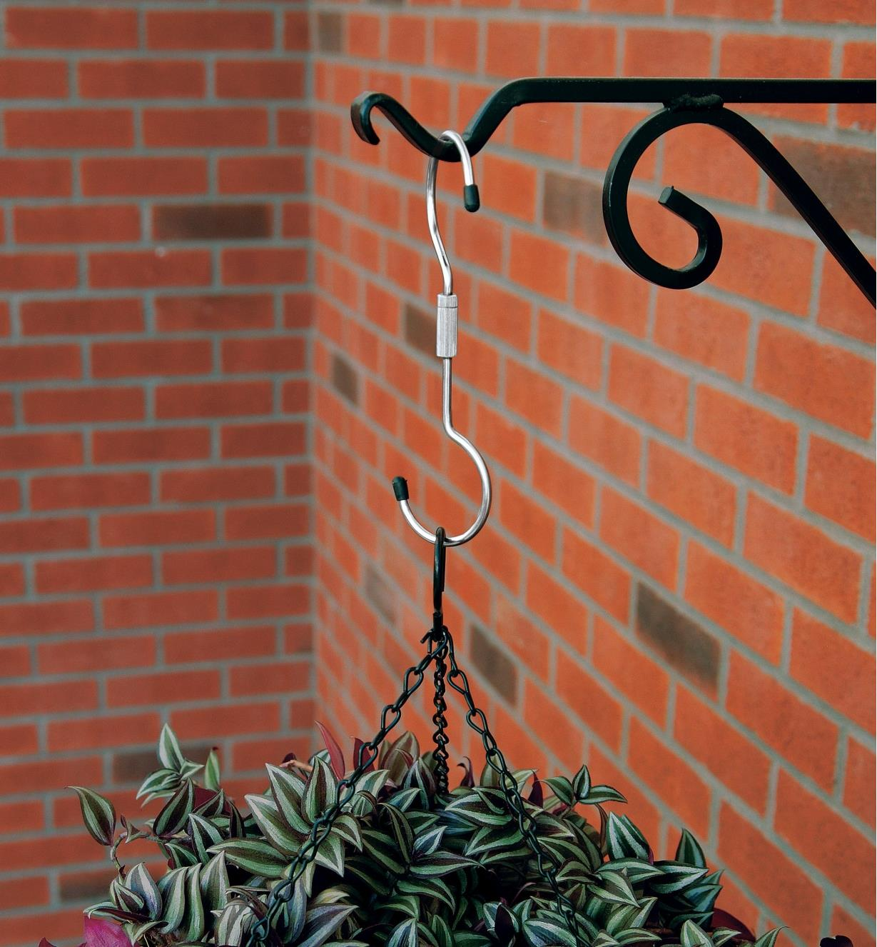 A swivel hook hanging a planter on a wall bracket