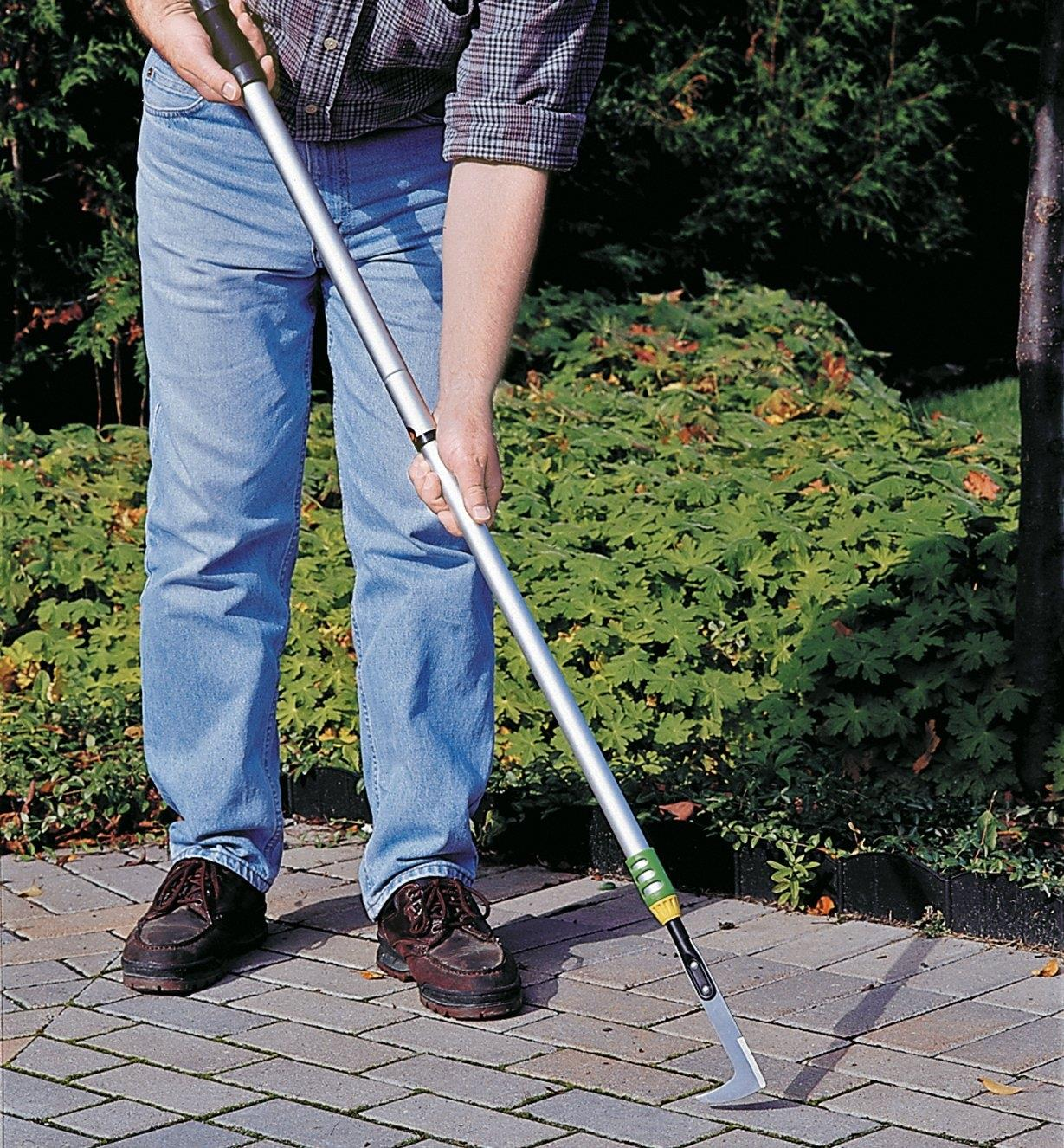 A man using the Telescoping Crack Weeder to remove weeds from between patio stones