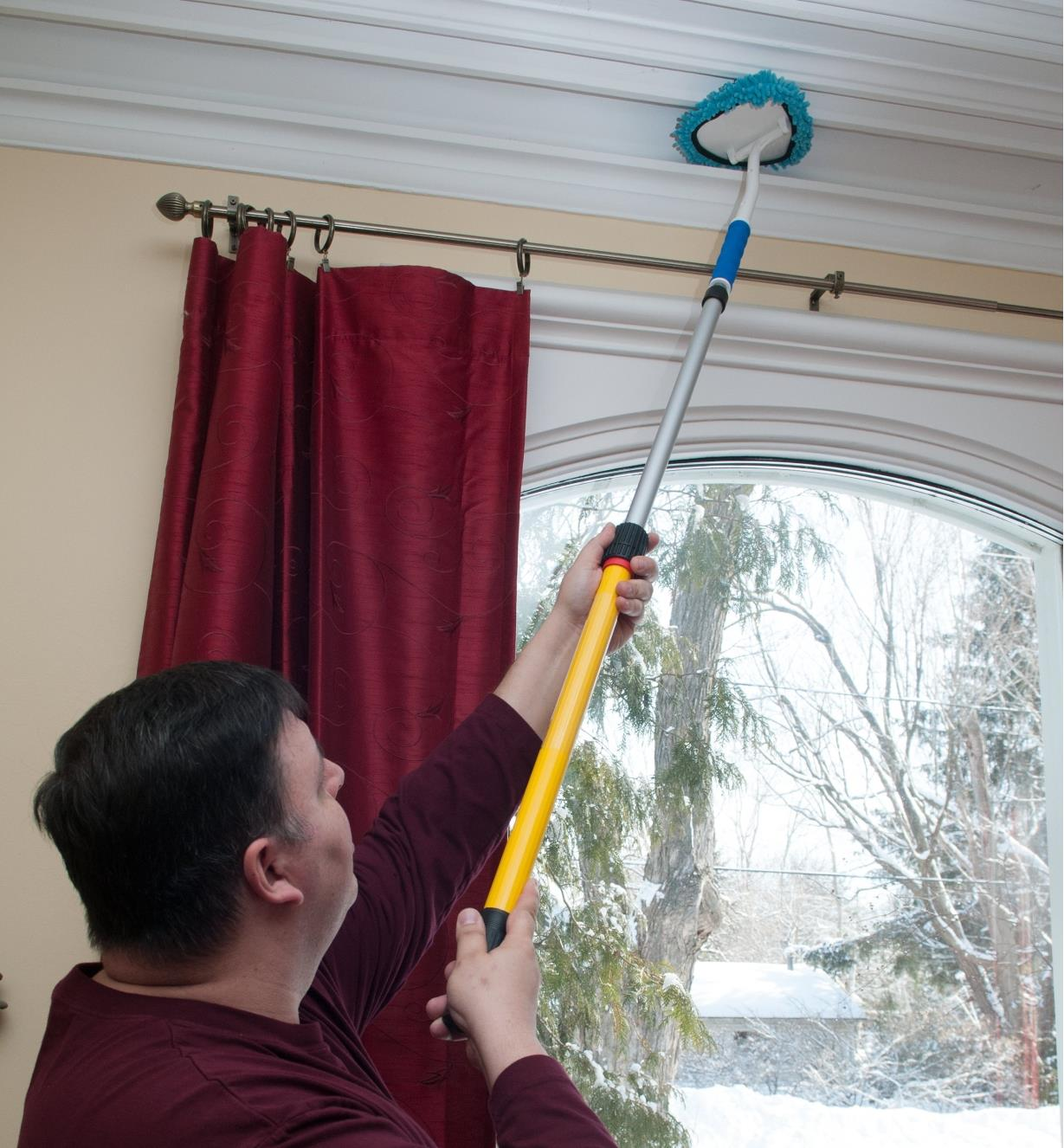 Using the 2' to 3 1/2' Extension Pole and a duster attachment to clean crown molding
