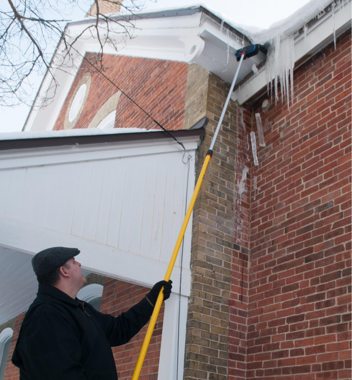 Using the 8' to 22 1/2' Extension Pole and a brush to clear icicles from eaves on a house