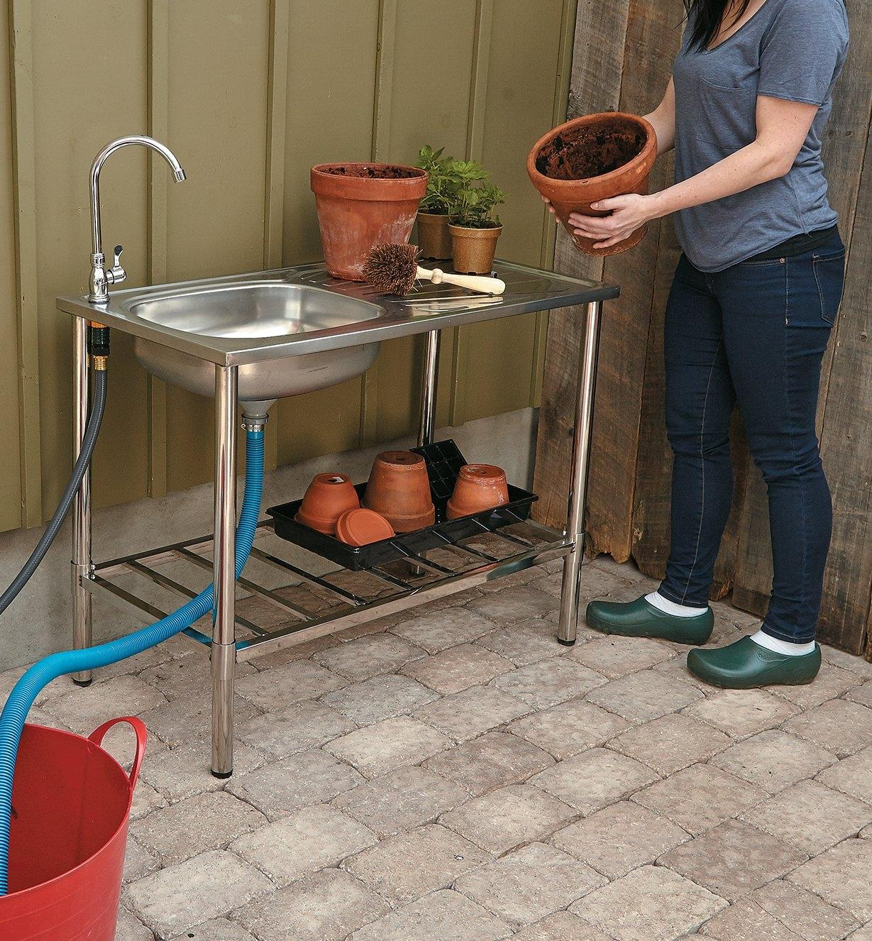 Stainless-Steel Outdoor Wash Table holding various sizes of pots on the top and lower shelf