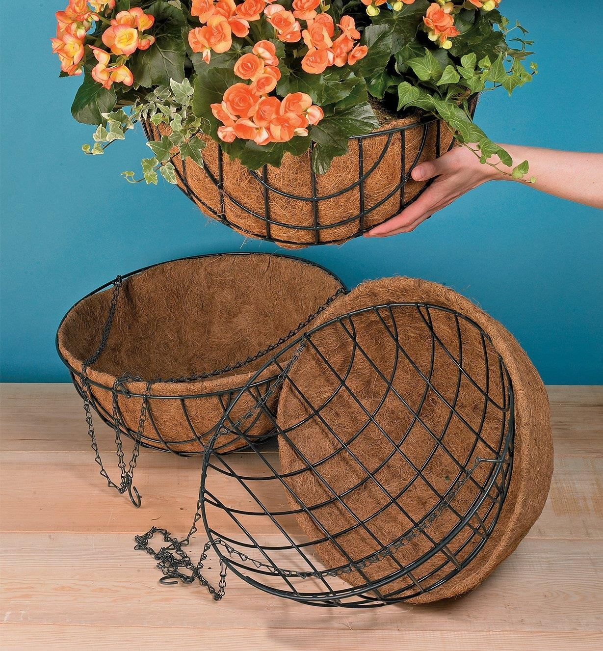 "Two empty 18"" hanging baskets on a table and one holding a plant being hung up"