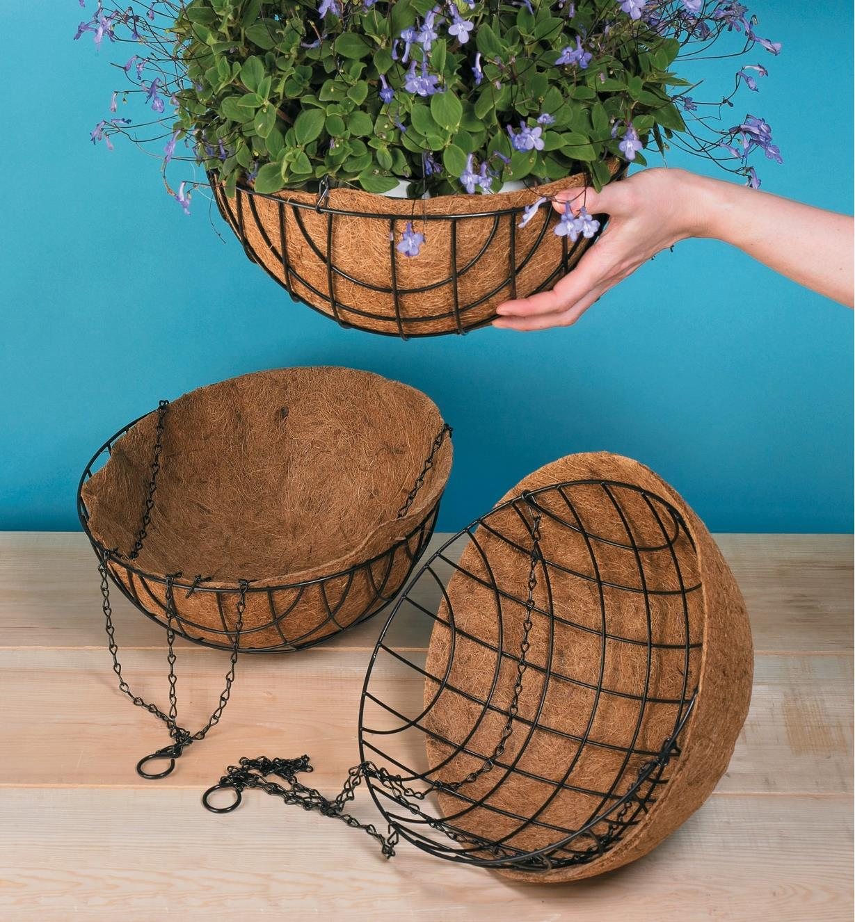 "Two empty 14"" hanging baskets on a table and one holding a plant being hung up"