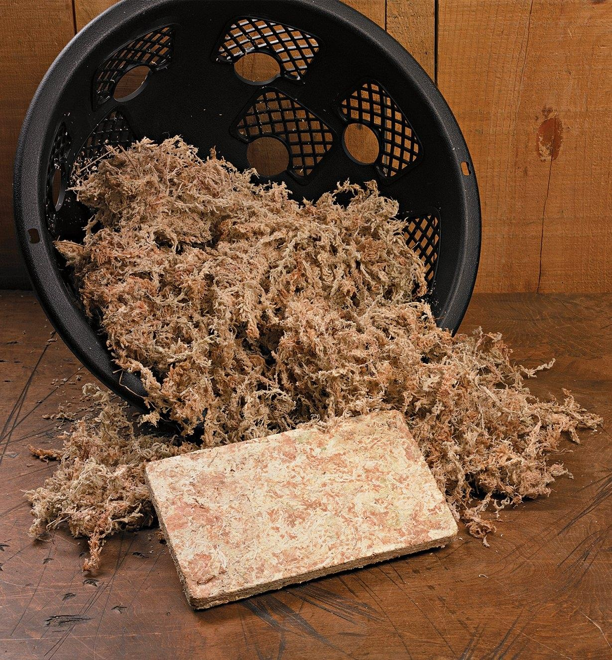 Compressed Sphagnum Moss packet in front of a basket filled with expanded moss