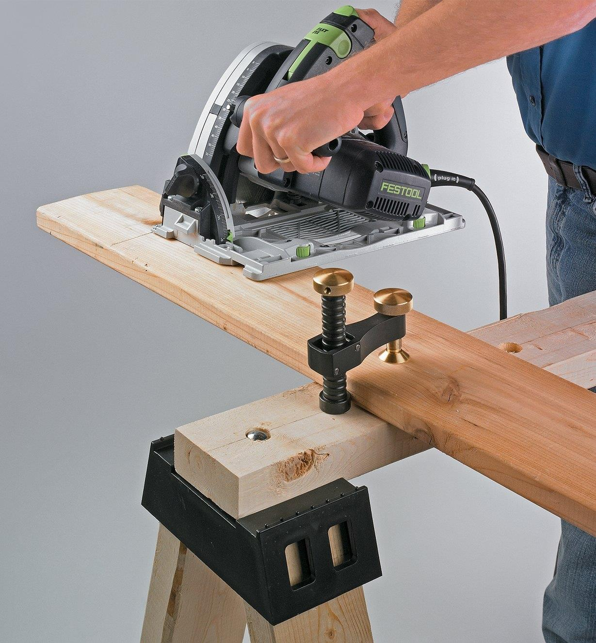 Veritas Surface Clamp holding a board to a sawhorse while the board is being cut with a circular saw
