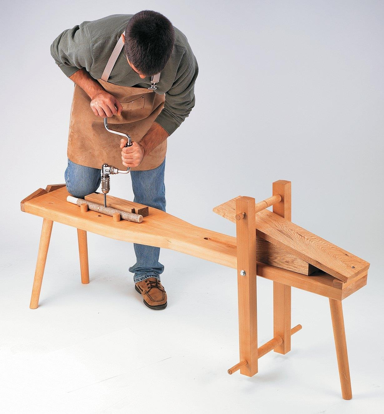 A man kneeling on a shaving horse uses a hand drill to bore a hole in a workpiece