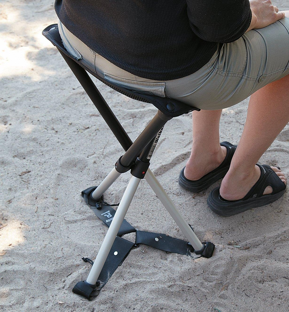 A woman sits on a Walkstool Comfort with the Walkstool Steady attached, sold separately.
