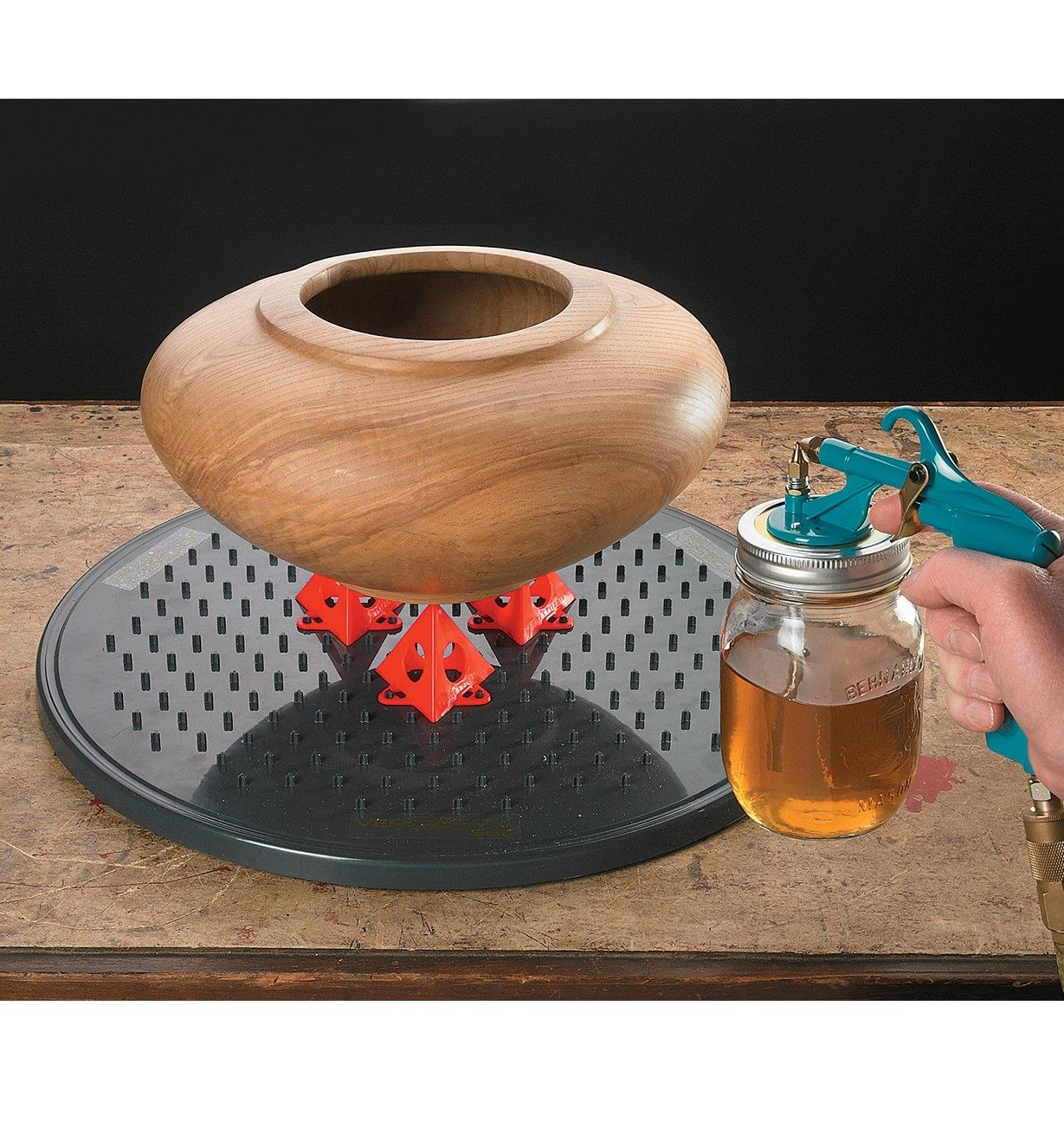 Spraying a wooden vase that is propped on a Versa-Spin Finishing Turntable with Painter's Pyramid supports