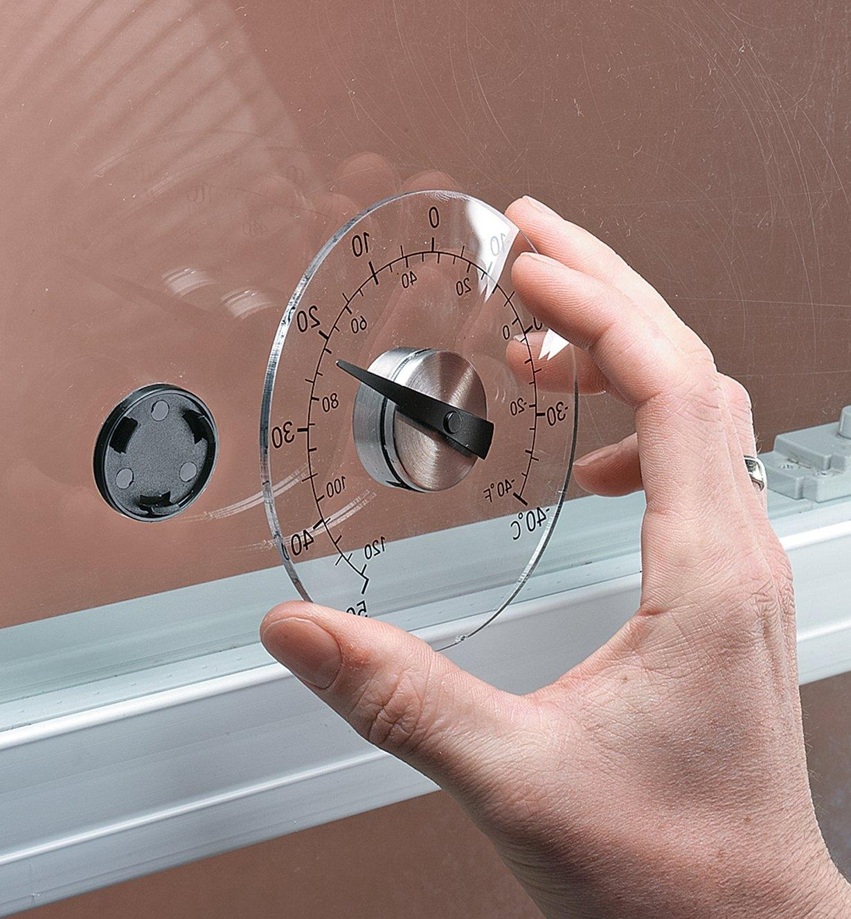 Mounting the Window-Mount Thermometer on the adhesive central hub attached to a windowpane