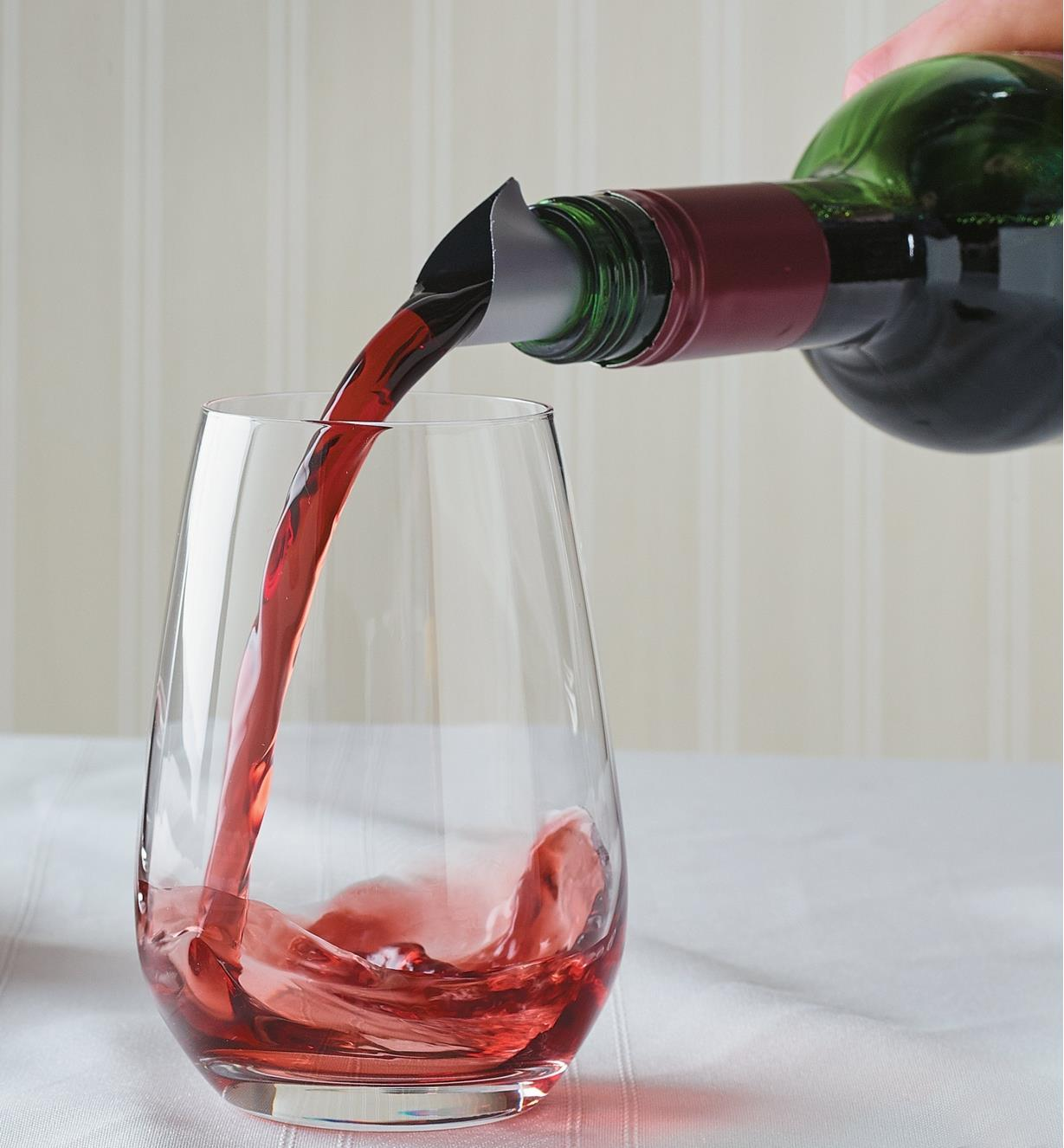 Pouring wine into a glass from a bottle fitted with a wine disc