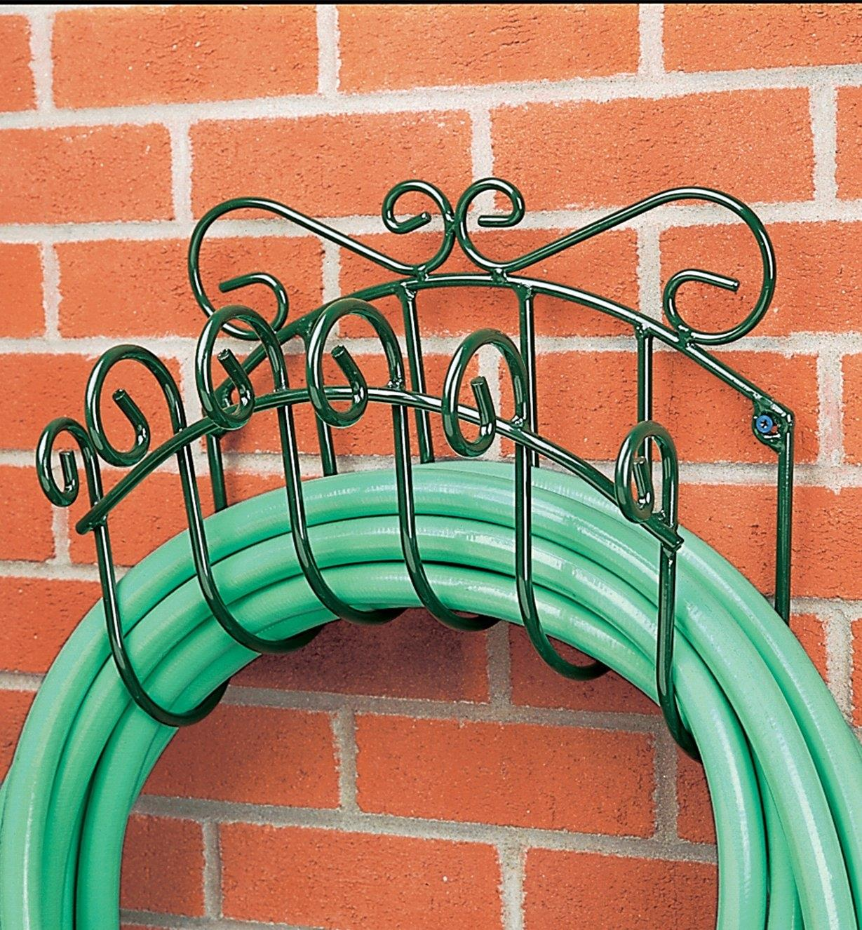 Wrought-Iron Hose Hanger with a hose coiled around it mounted on a wall