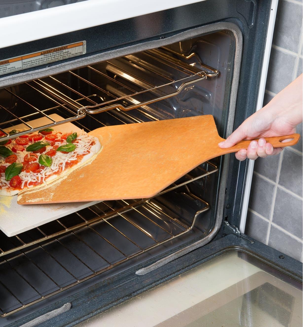 Personne déposant une pizza dans le four à l'aide d'une planche à pizza