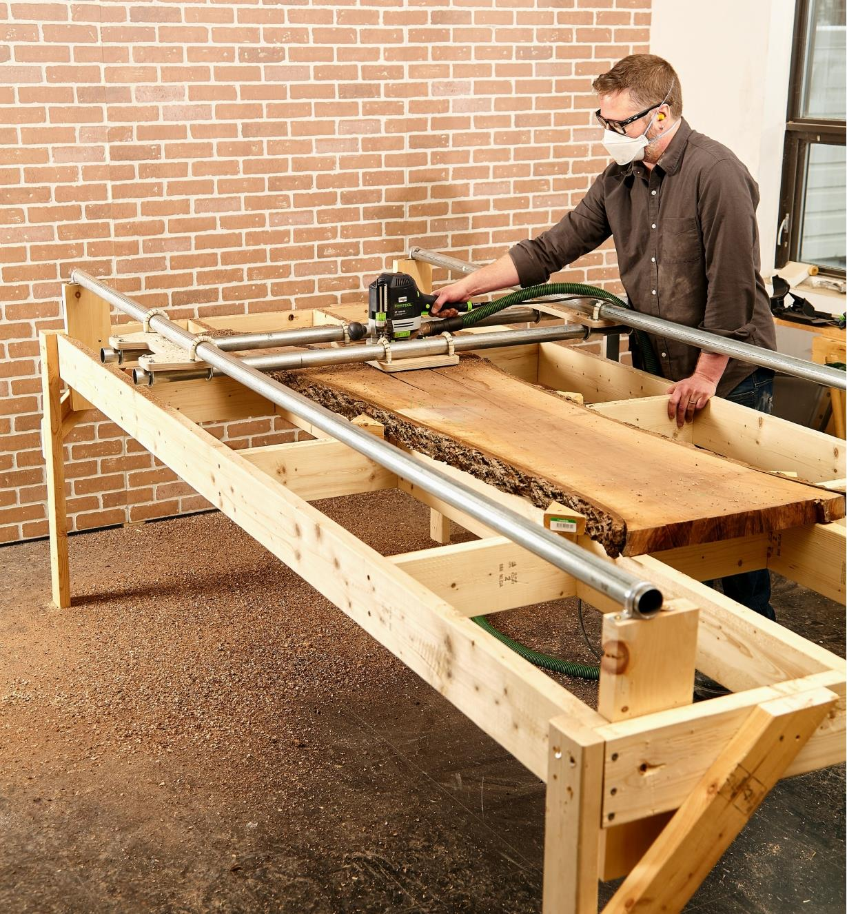 A wood slab is flattened using a router and the assembled router sled