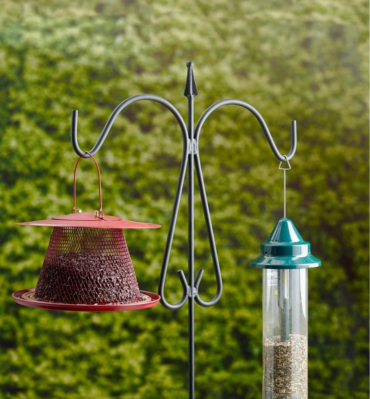 Two bird feeders hung from a double garden hanger