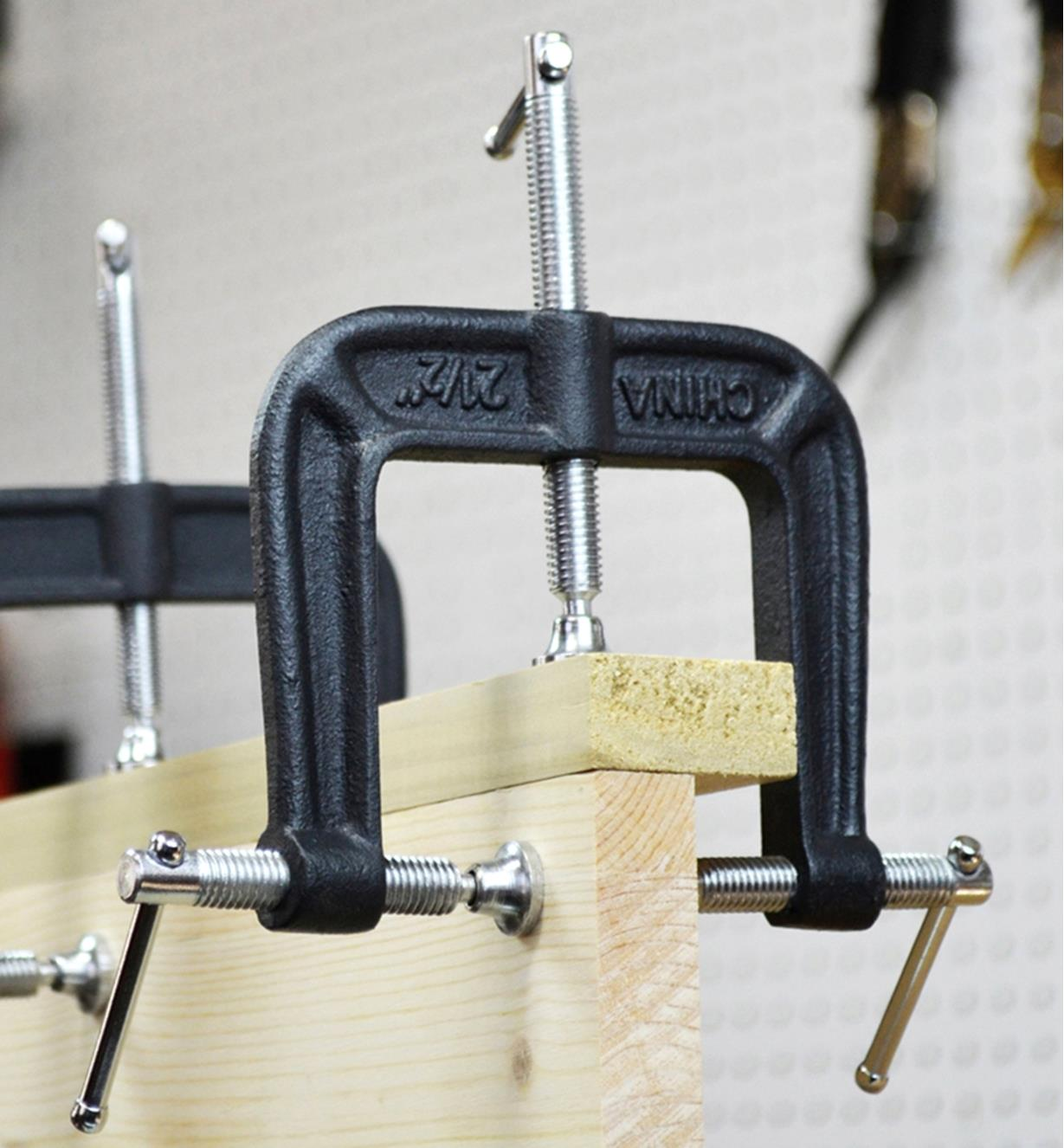 A pair of Bessey three-way edge clamps being used to hold two pieces of wood together perpendicular to each other
