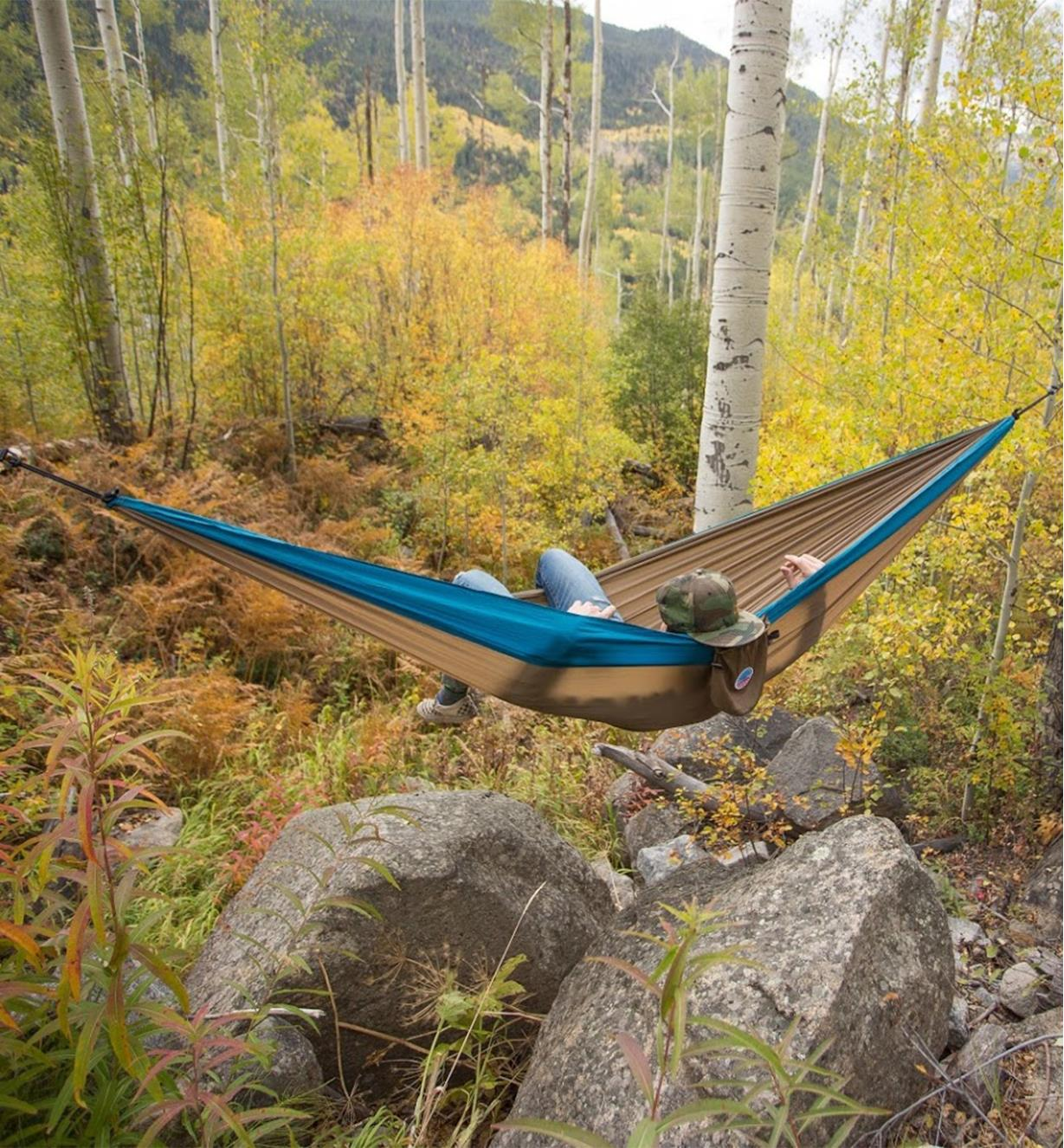 A person lying in a taupe/teal hammock hung between two trees in a forest