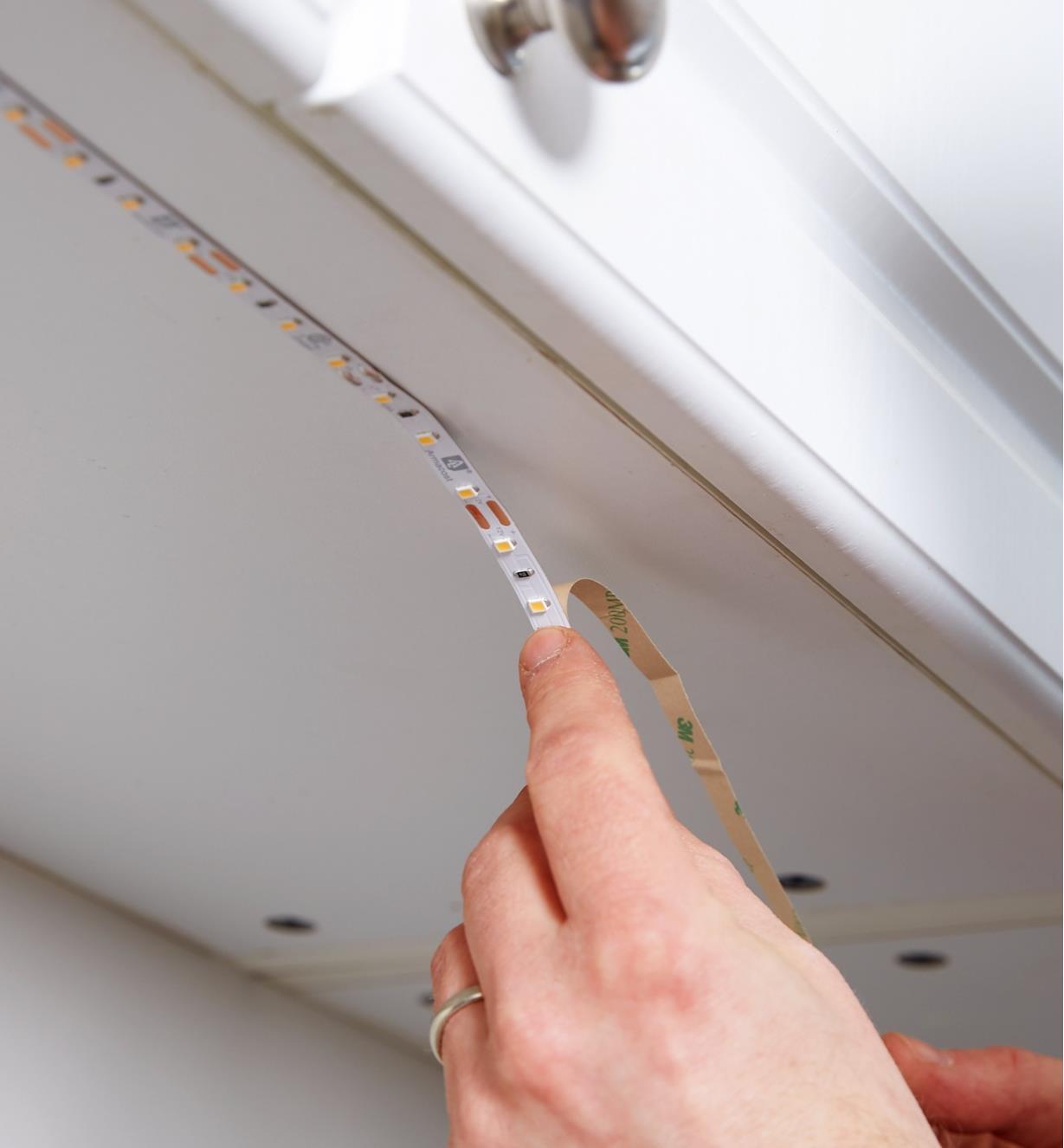 Personne fixant le luminaire-ruban sous une armoire de cuisine grâce au dos autocollant