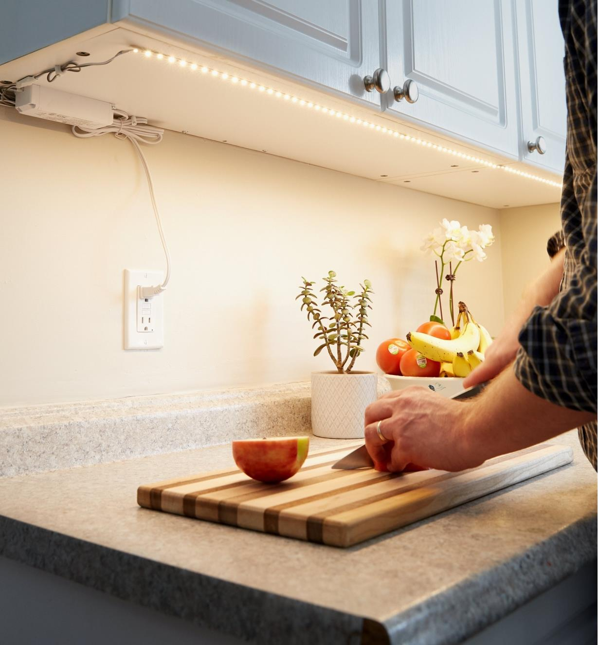 A plug-in LED tape lighting kit mounted under kitchen cupboards to light a countertop