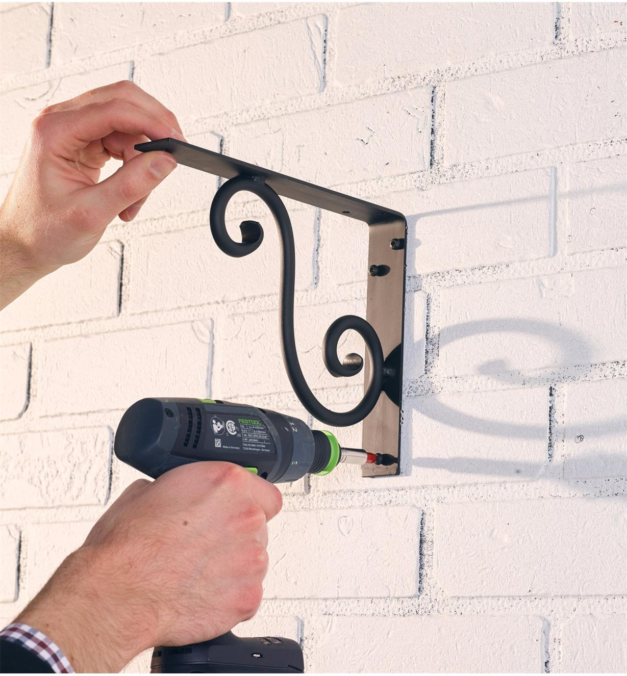 Using an electric drill to mount a large scroll bracket to a wall