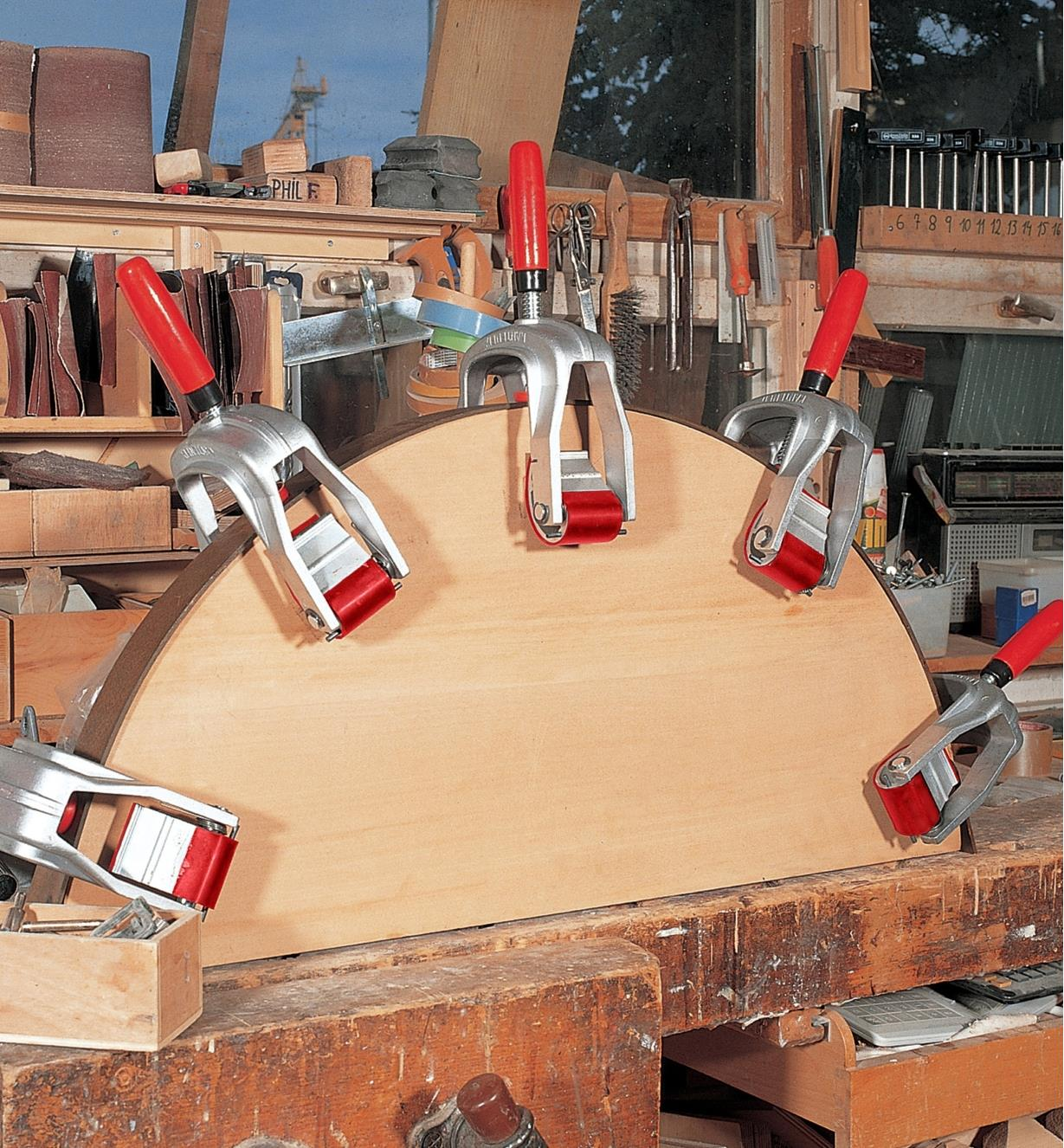 Five Bessey edge clamps being used to hold edging in place on a curved workpiece