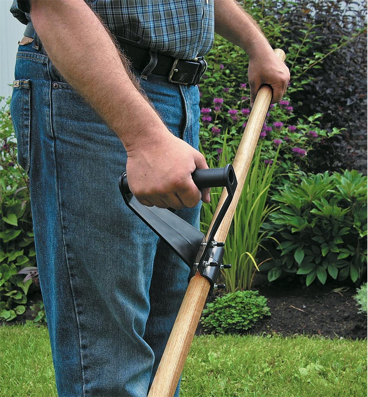 A man using a BackSaver Grip attached to a long-handled tool