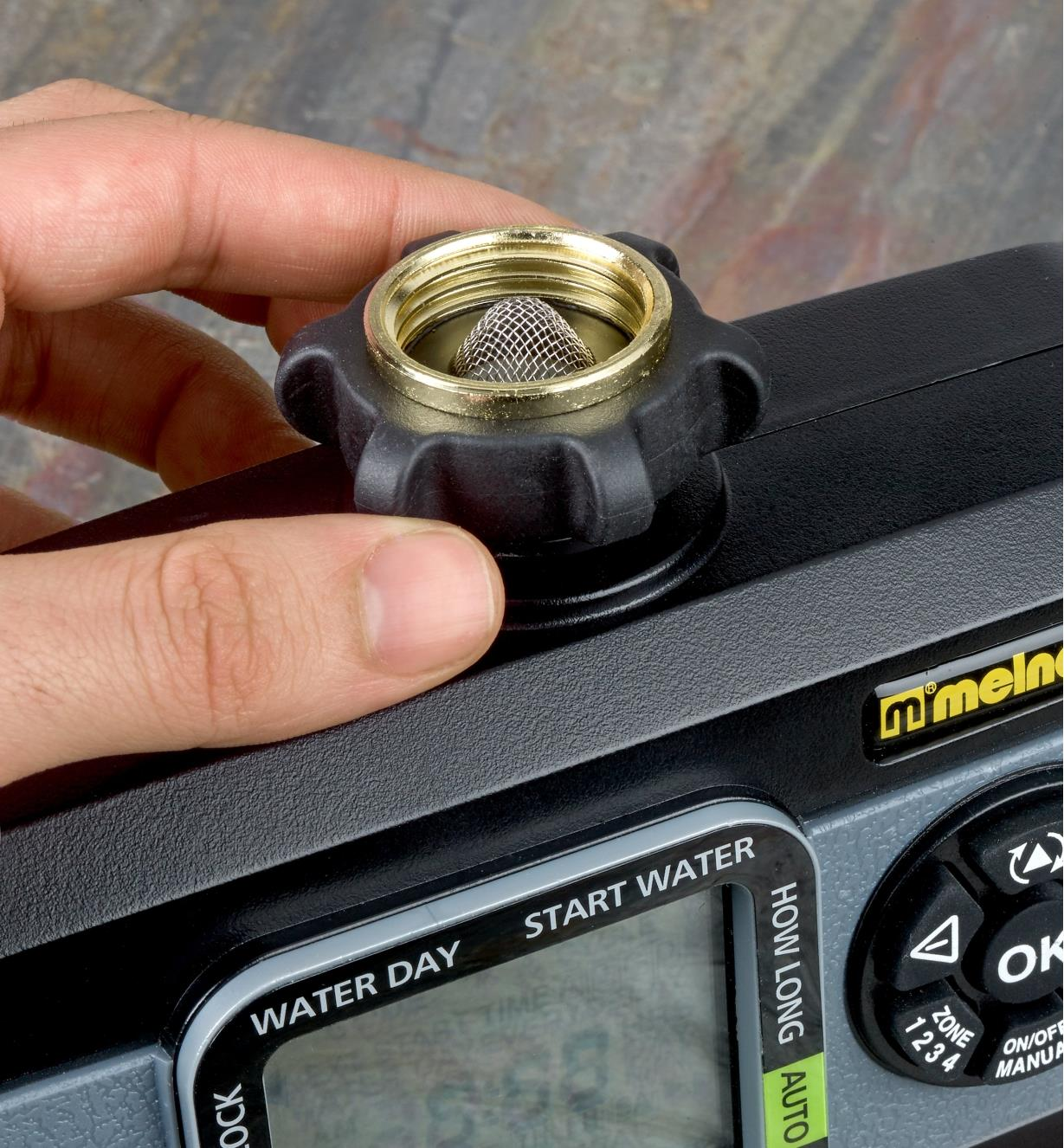 Close-up of electronic water timer faucet connector with filter and ridges for grip