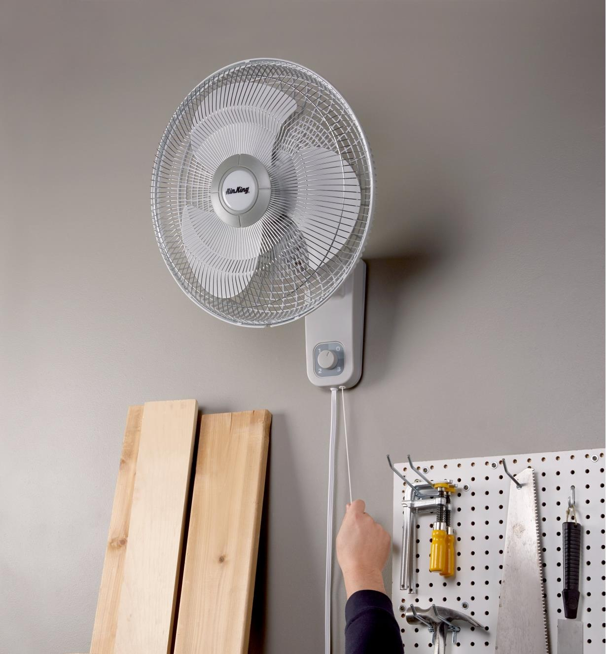 Using the pull-cord to adjust fan speed on the Air King fan installed high on a wall