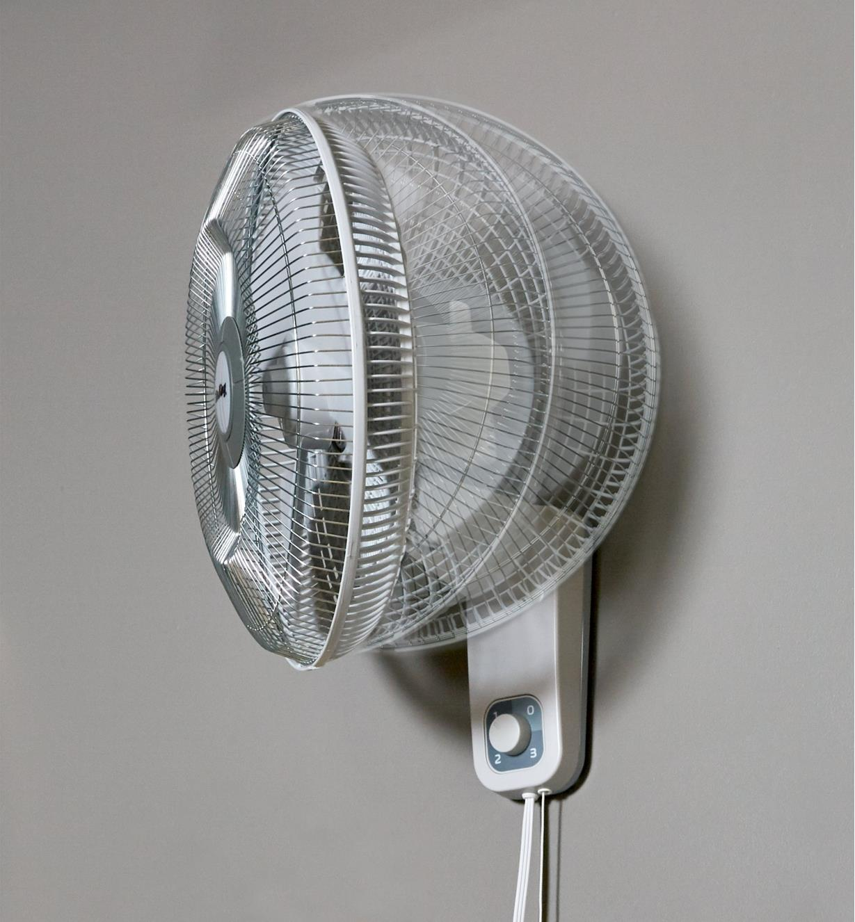 Ghosted image of the oscillating head of the Air King wall-mount fan