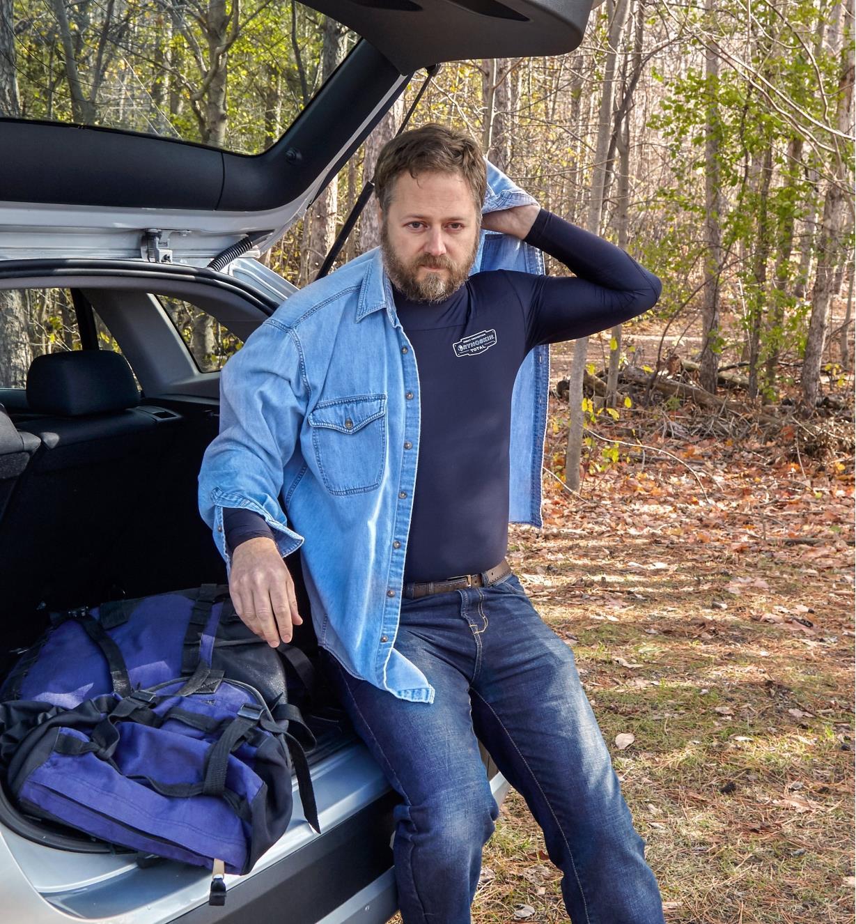 Man putting on a regular shirt over a Rynoskin shirt