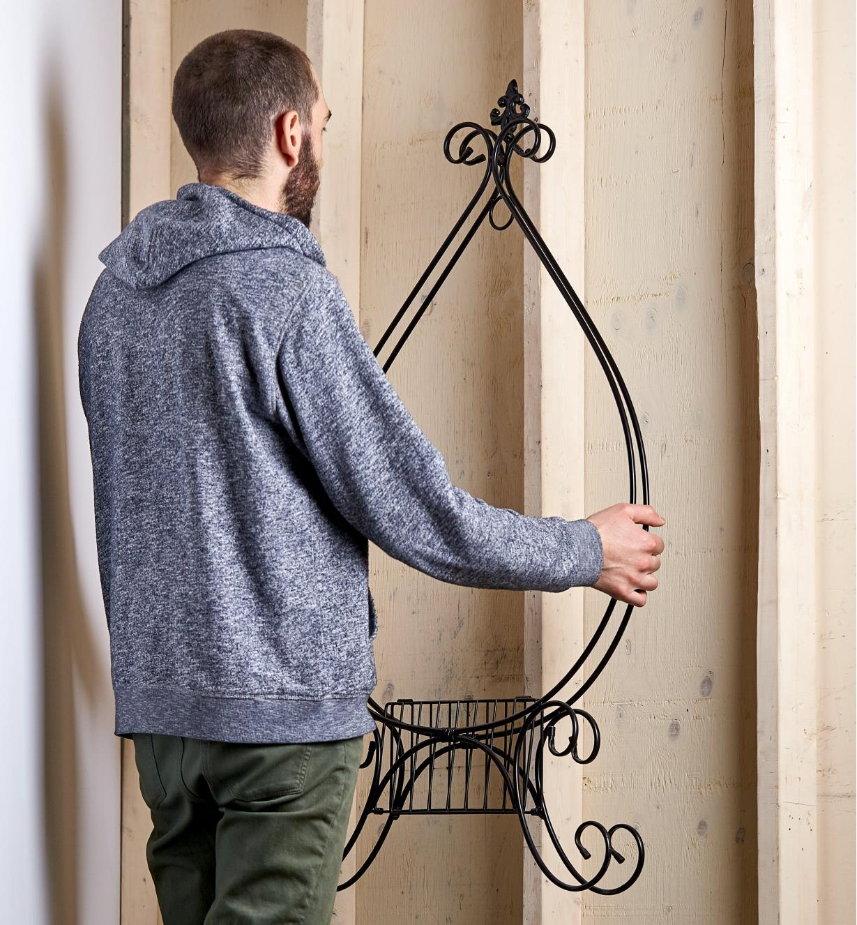 A man carrying the folding plant stand into a shed