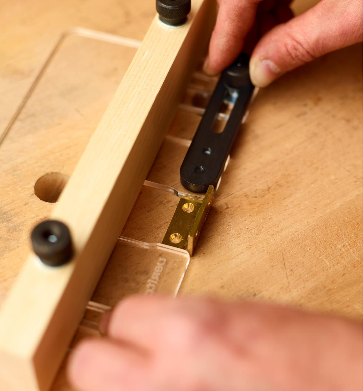 Setting the cabinet hinge template's adjustable opening to match the exact length of a cabinet hinge