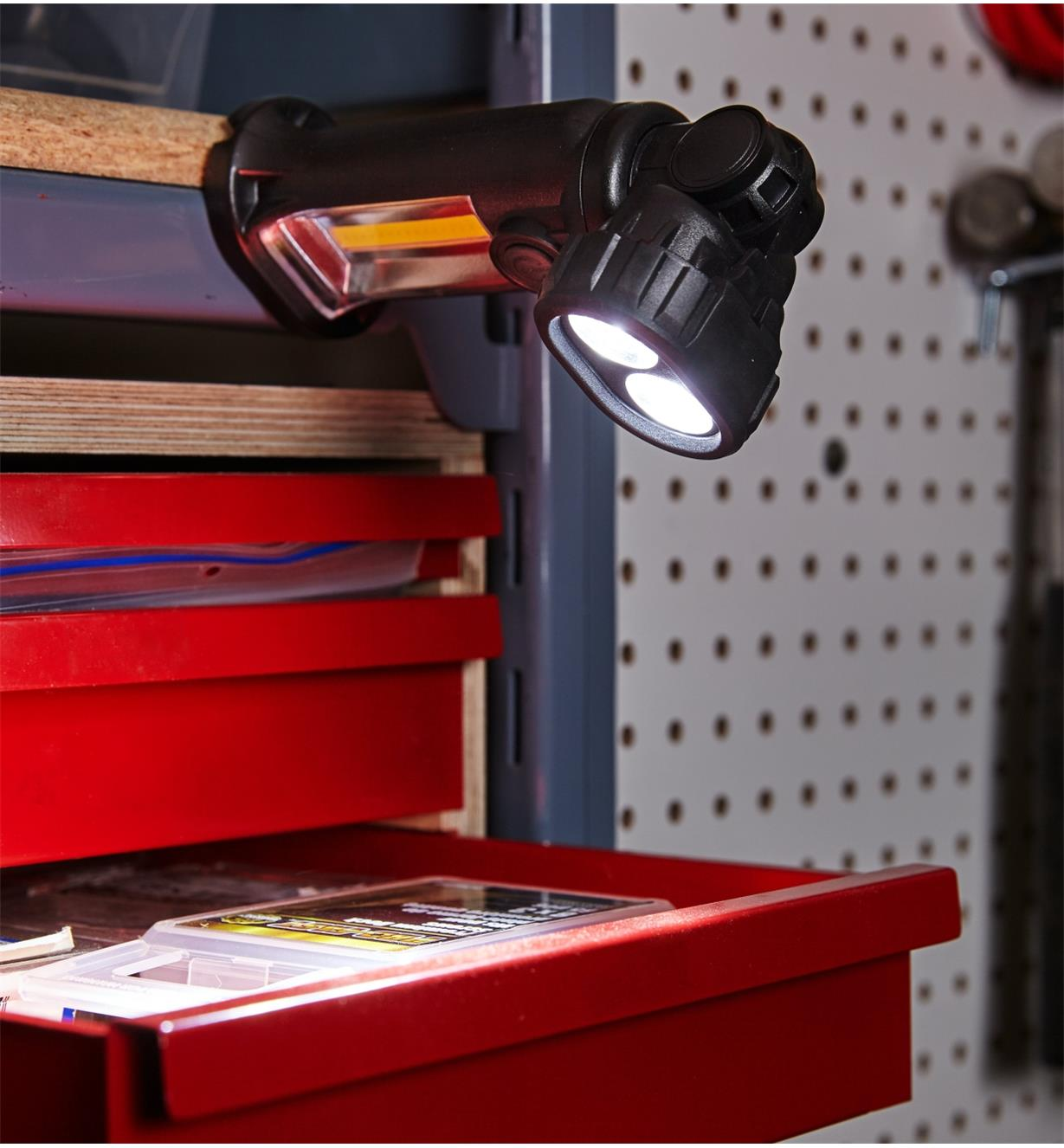 Easy-to-Aim Work Light affixed to metal shelving, illuminating a tool cabinet drawer