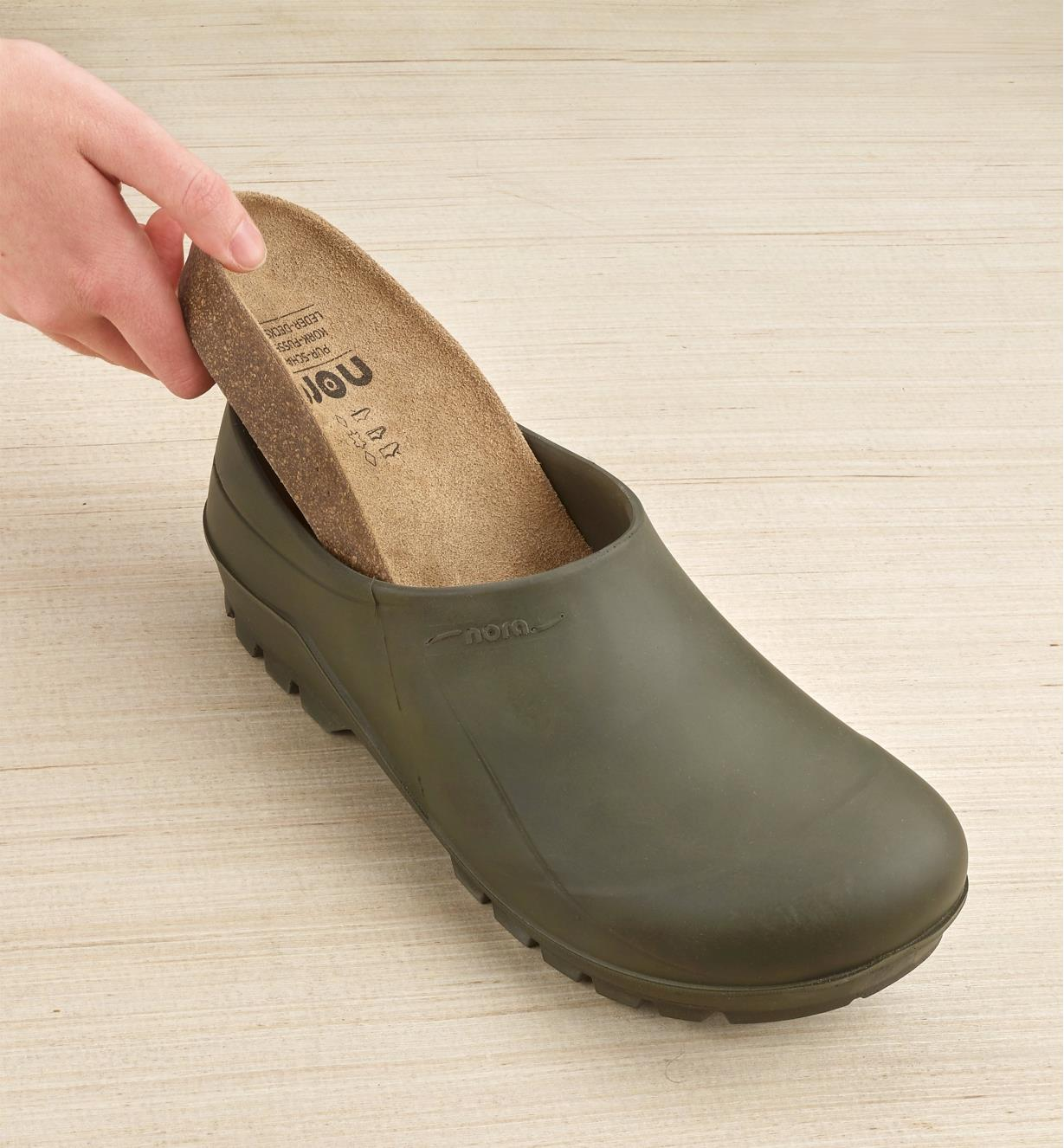 The removable cork insole being slipped into a European garden clog