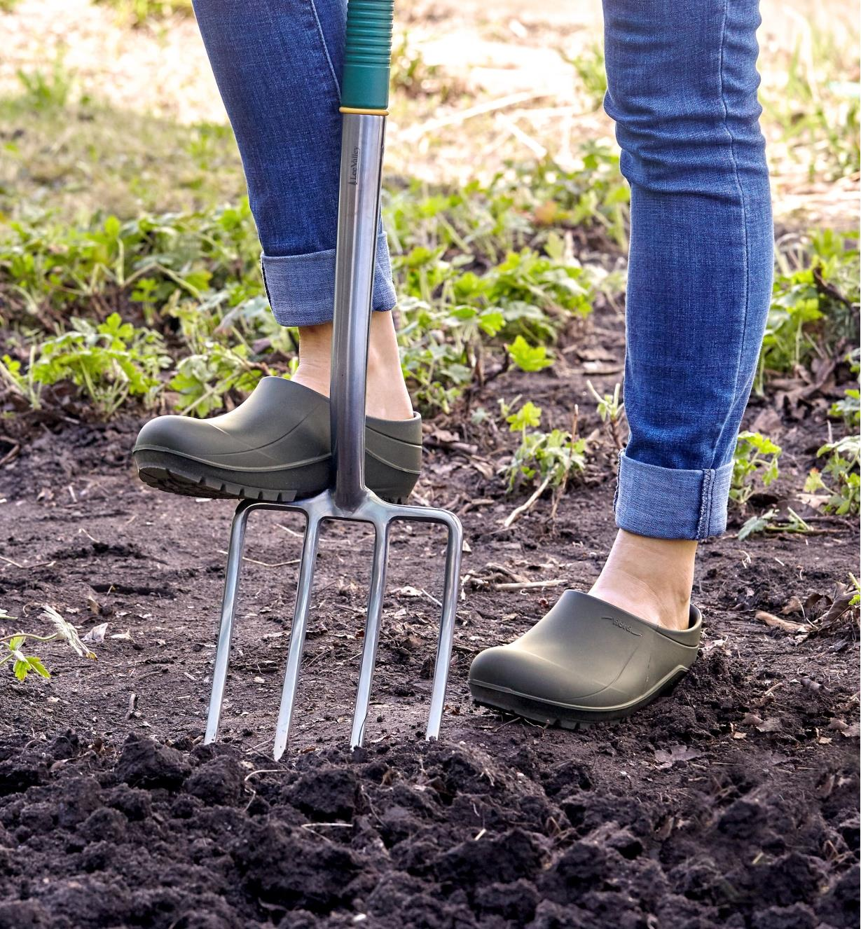 A woman wearing European garden clogs bears down on a garden fork to drive it into the soil