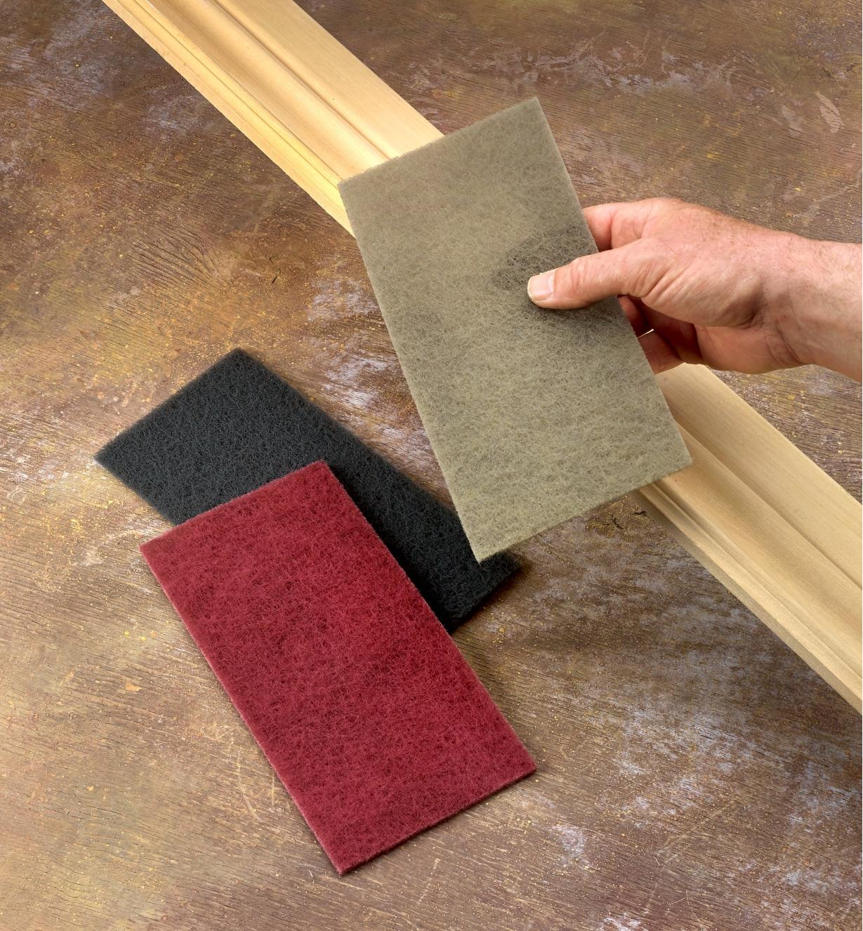 A woodworker prepares to sand a piece of molding with Mirlon Total abrasive pads in various grits